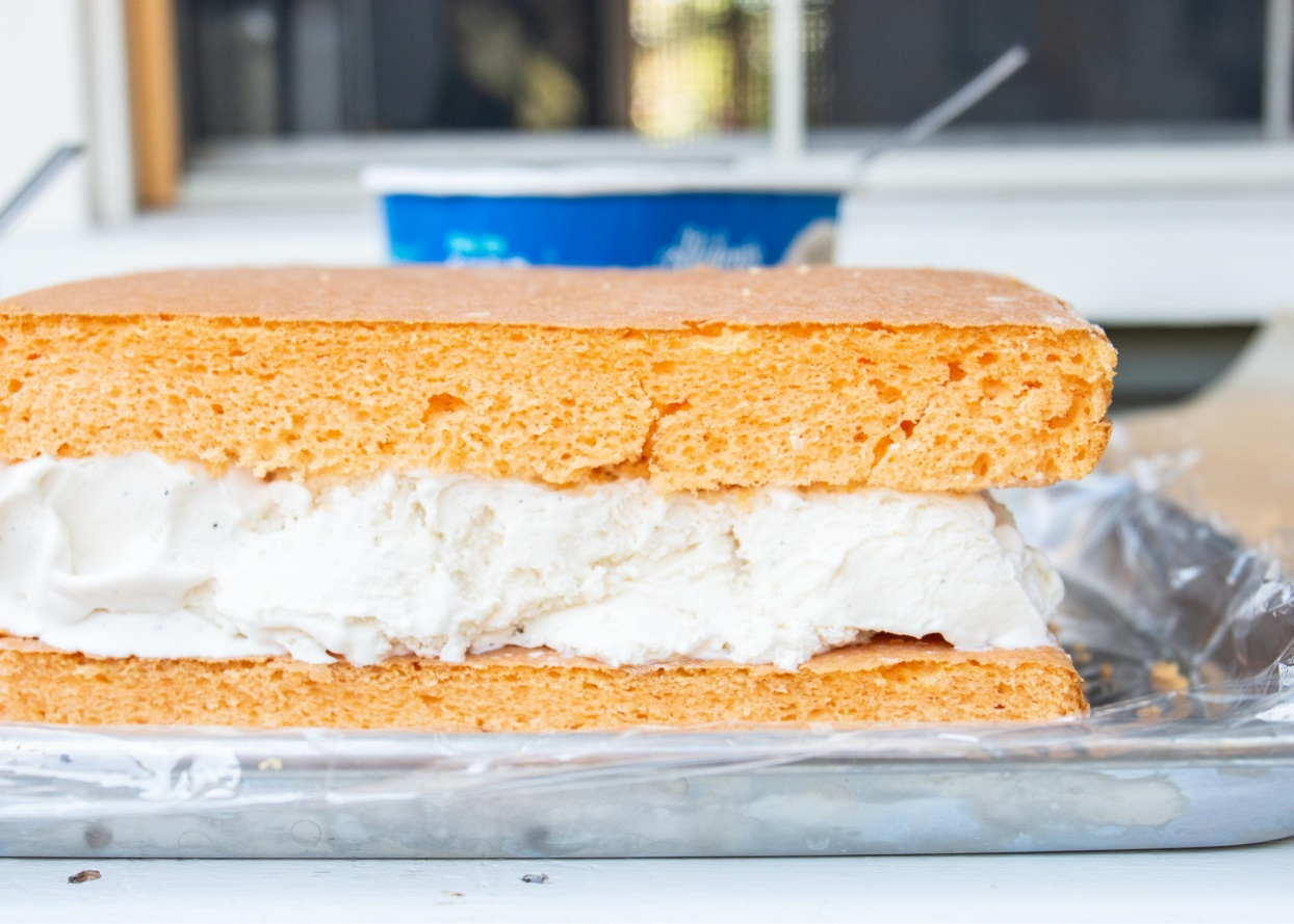 two layers of orange cake with ice cream sandwiched in-between