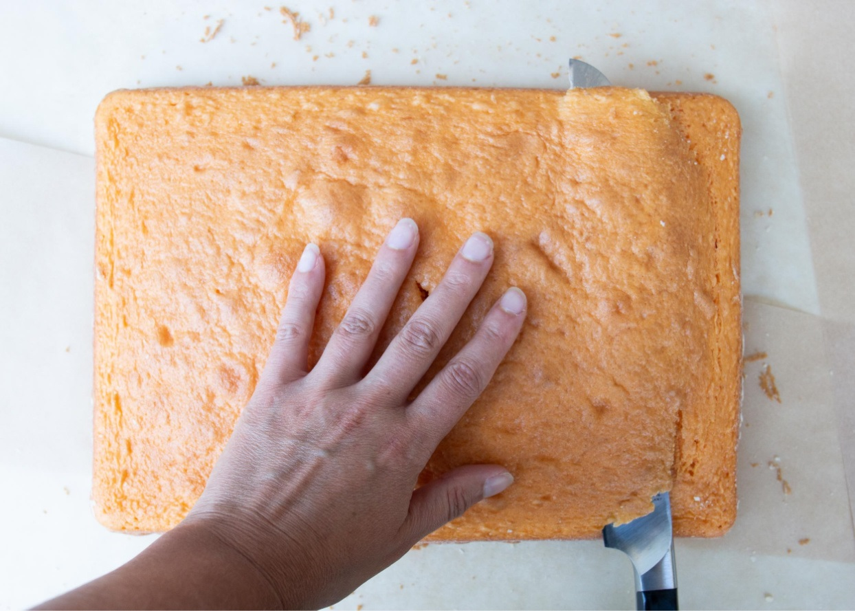 trimming off the domed top of an orange sheet cake