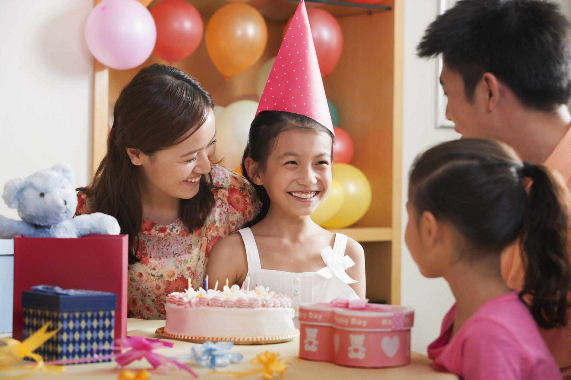 family celebrating daughter''s birthday with cake and balloons