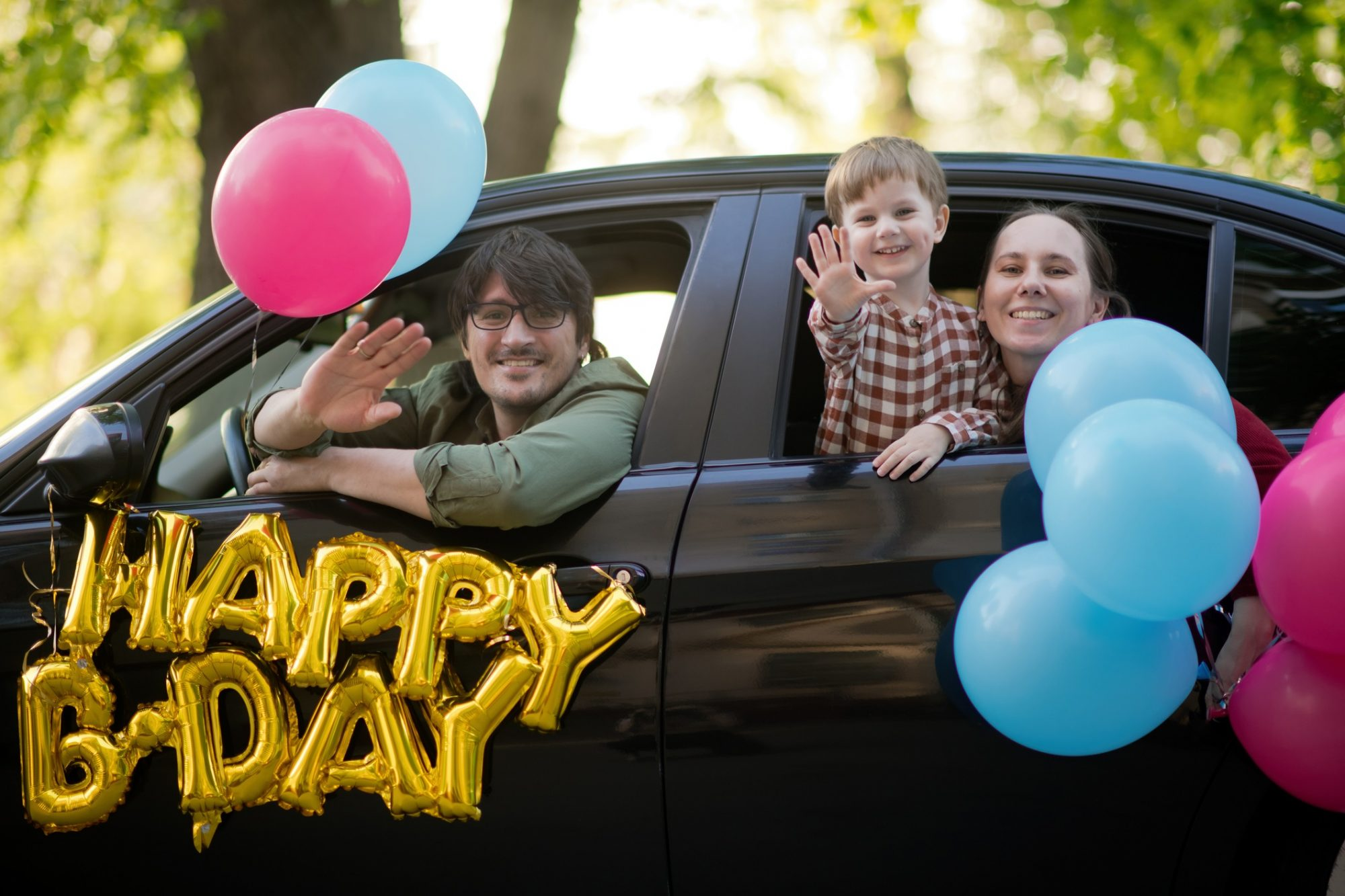 family waving hello during a birthday car parade during pandemic