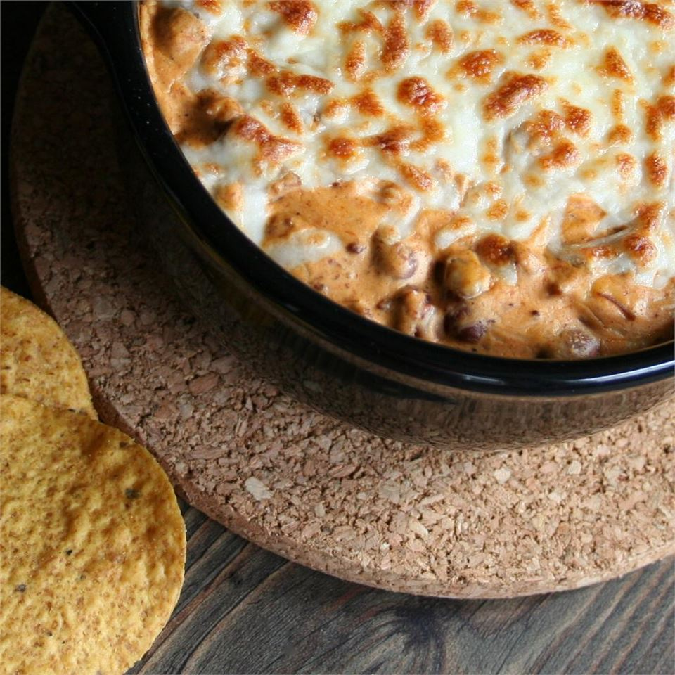 Cheesy Chili Dip II in a black bowl served with tortilla chips