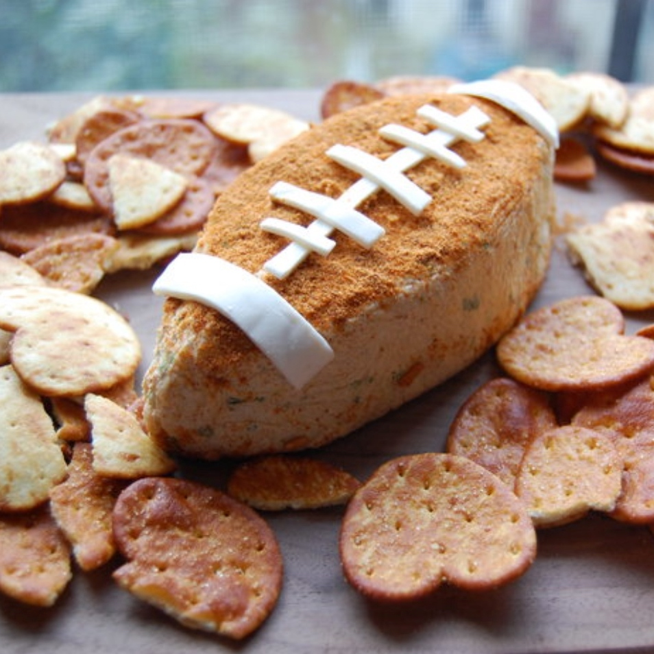 A cheese ball shaped like a football on a platter with crackers