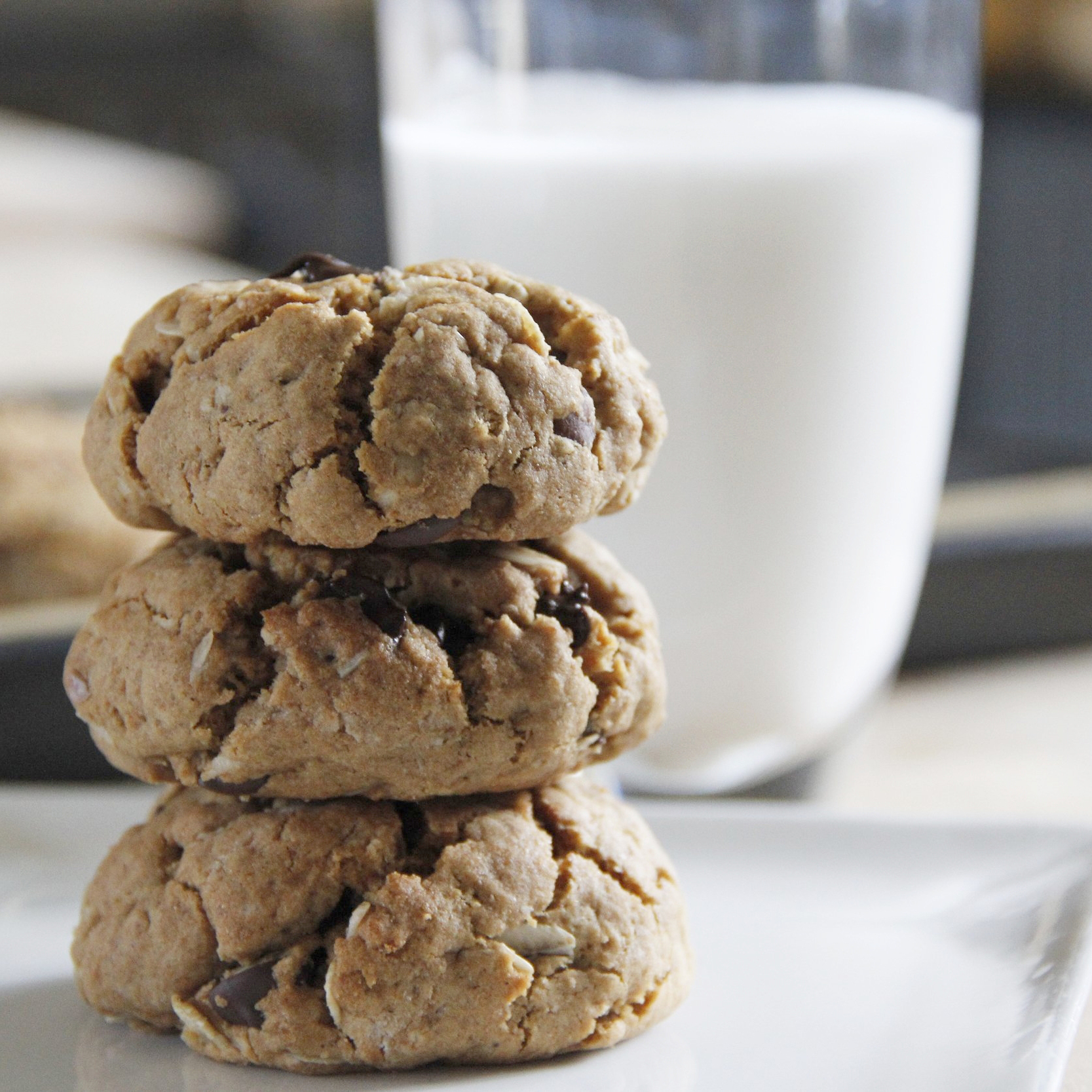 Chocolate Chip Cookies stacked up next to a glass of milk