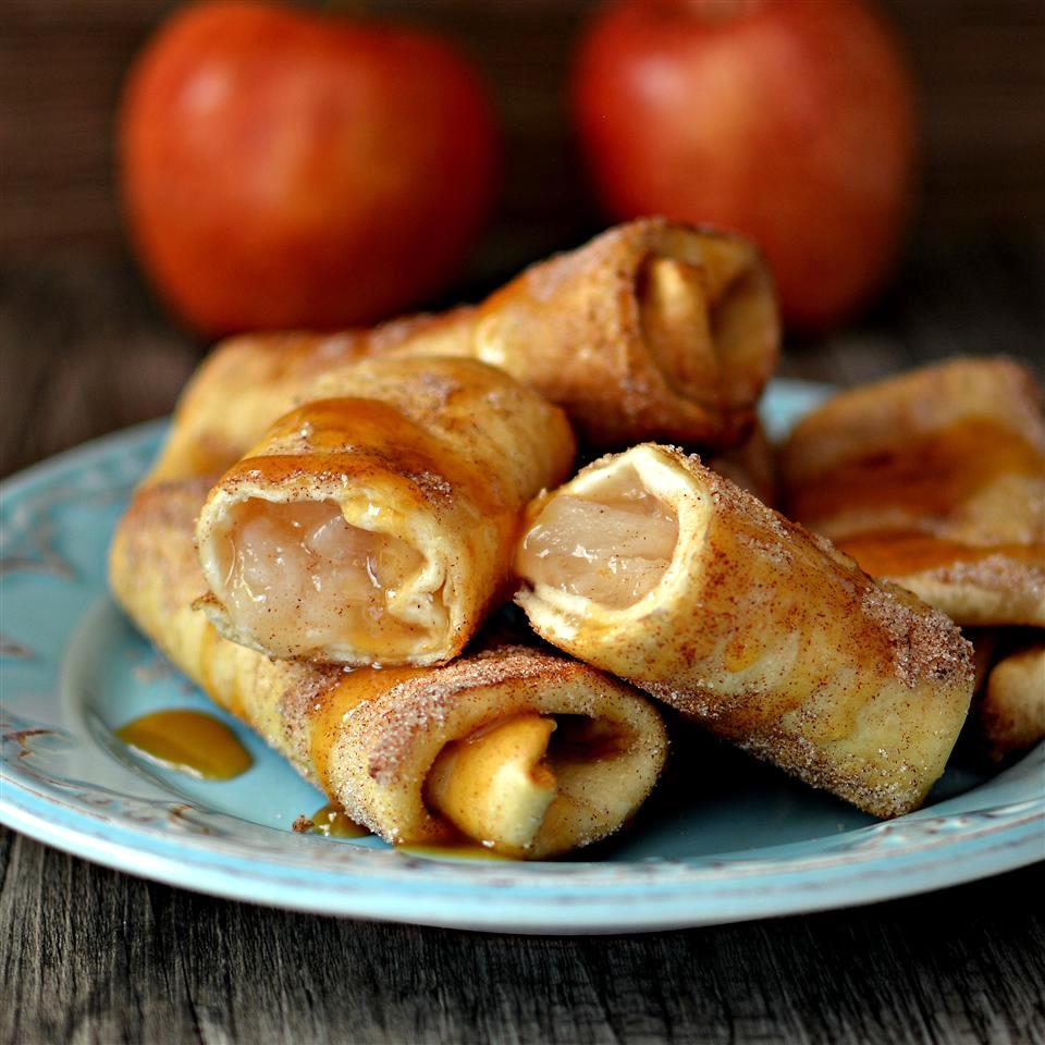 Apple Cinnamon Chimichangas on a plate in front of red apples