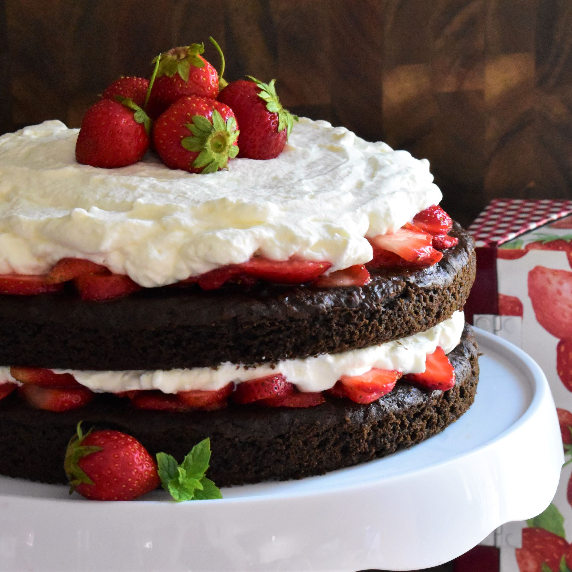 a two-layer Chocolate Strawberry Shortcake on a white cake stand
