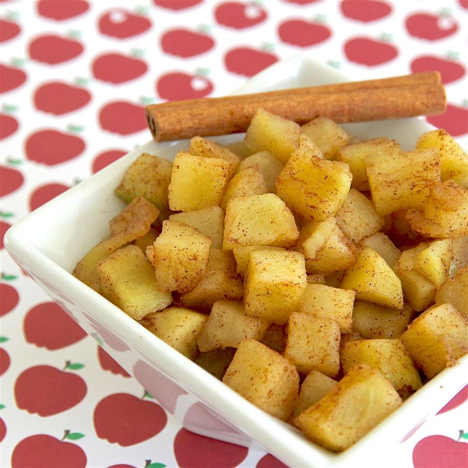 Cinnamon Apples with a cinnamon stick in a white dish
