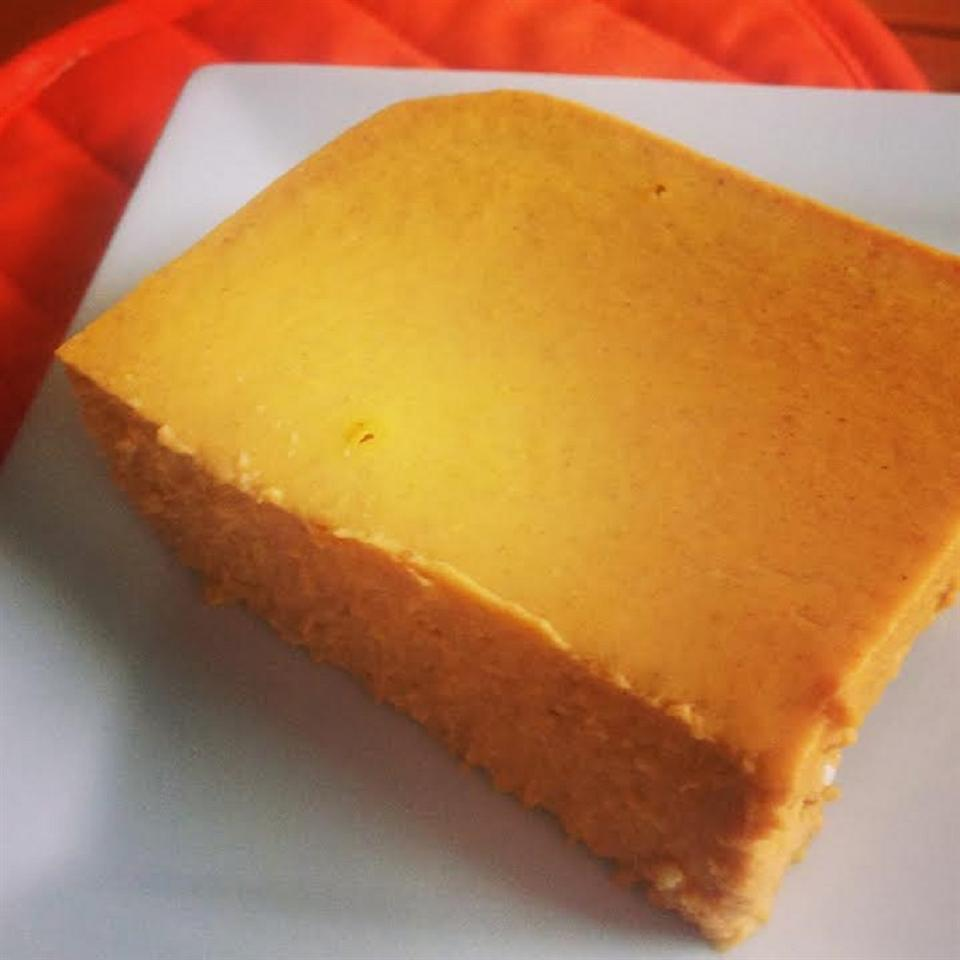 Slice of Low-Carb Pumpkin Cheesecake Bars on white plate with red oven mitt in background