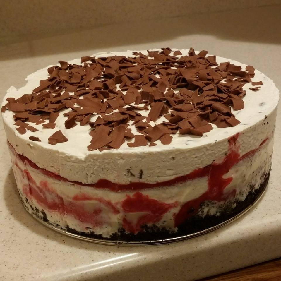 A layered Cranberry Ice Cream Swirl Cake sits on a kitchen counter