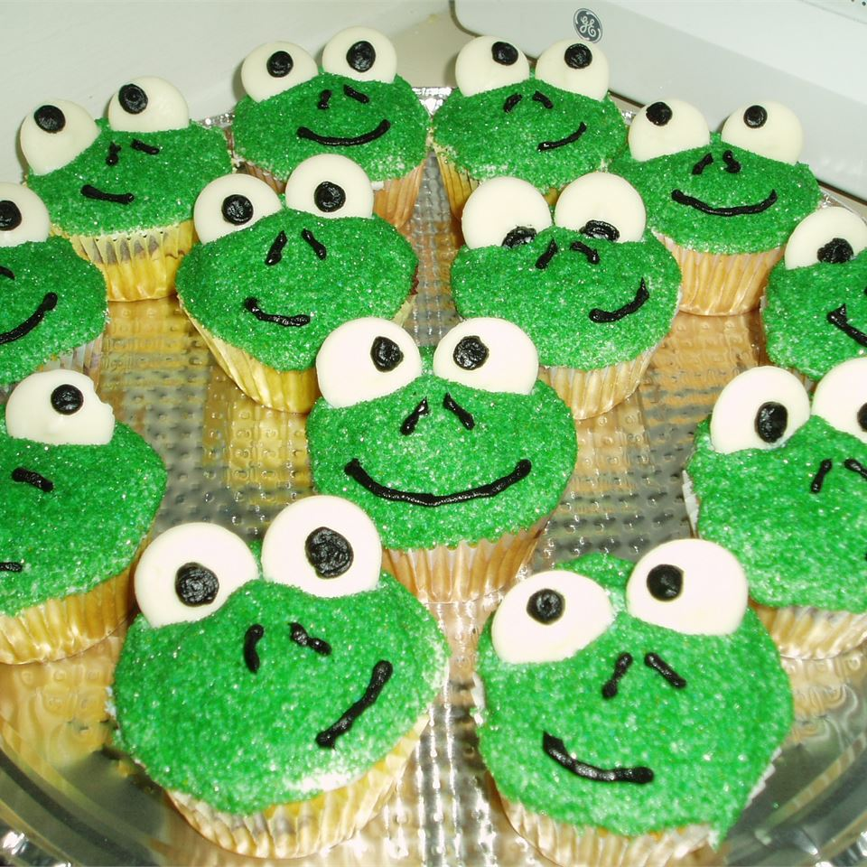 a platter of Frog Cupcakes with green faces, white eyes, and smiles