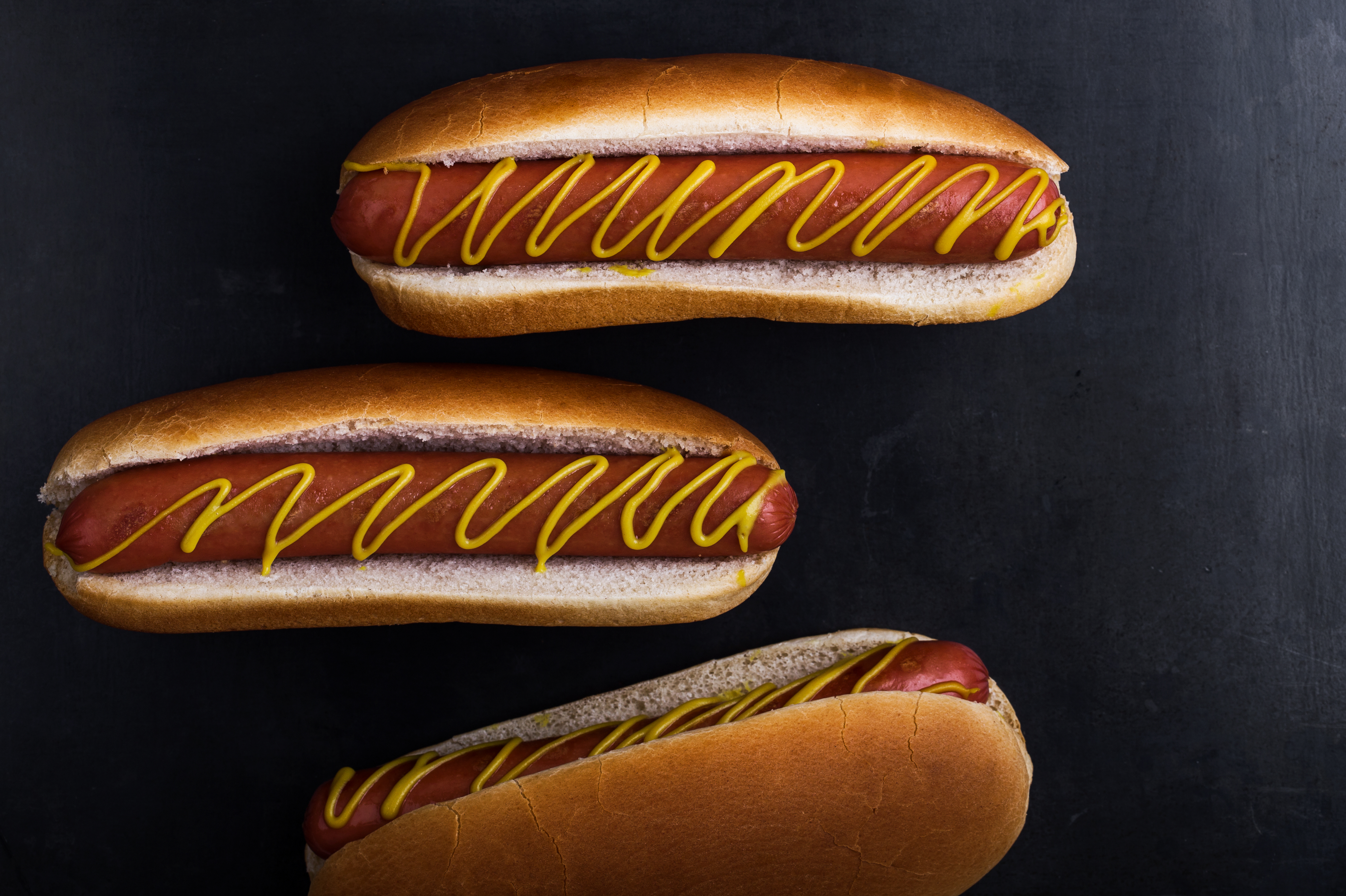 Hot dogs with mustard on gray background viewed from above