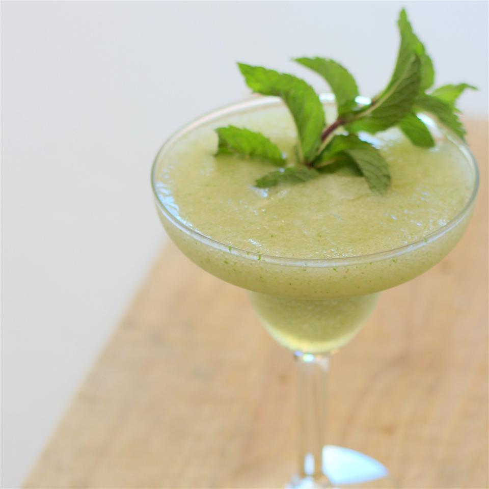 a margarita glass filled with Frozen Derby Mint Juleps and a sprig of mint