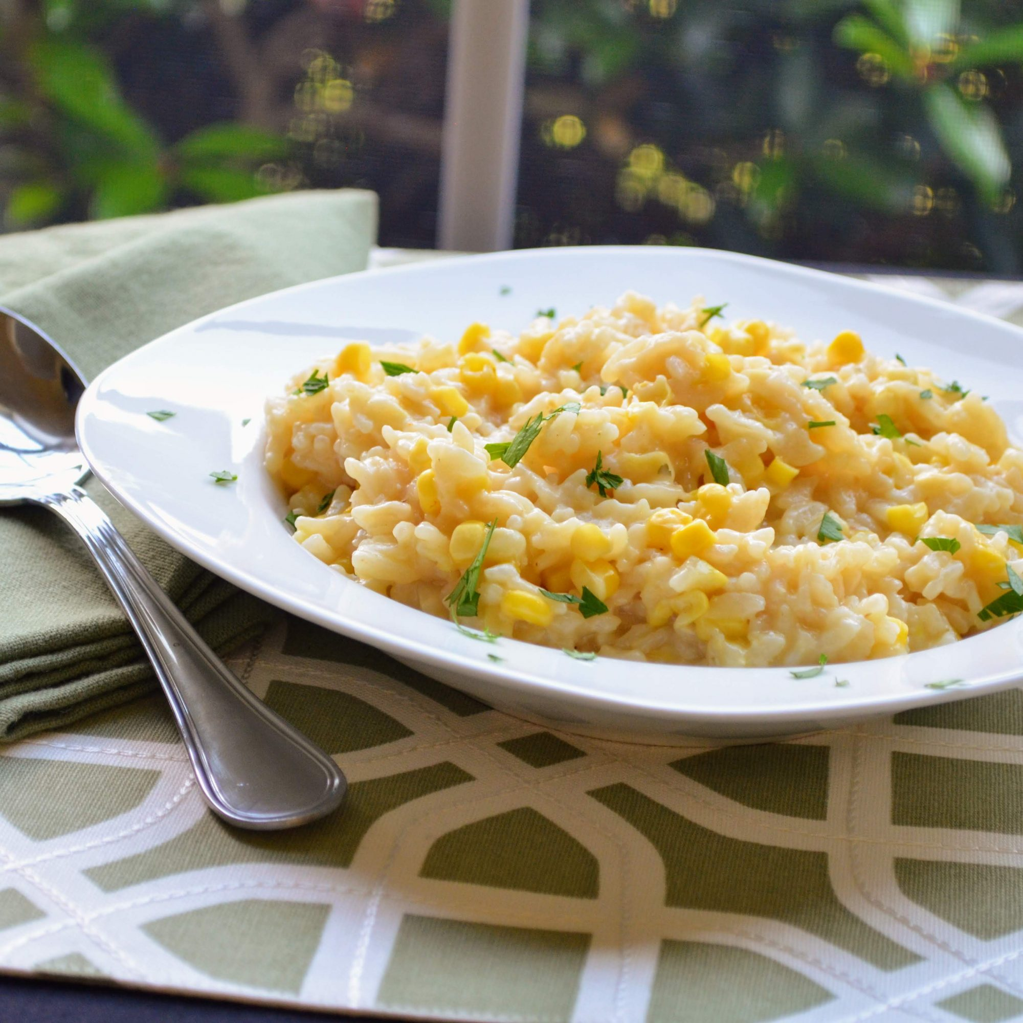 a bowl of Instant Pot® Fresh Corn Risotto on a place mat with a napkin and spoon