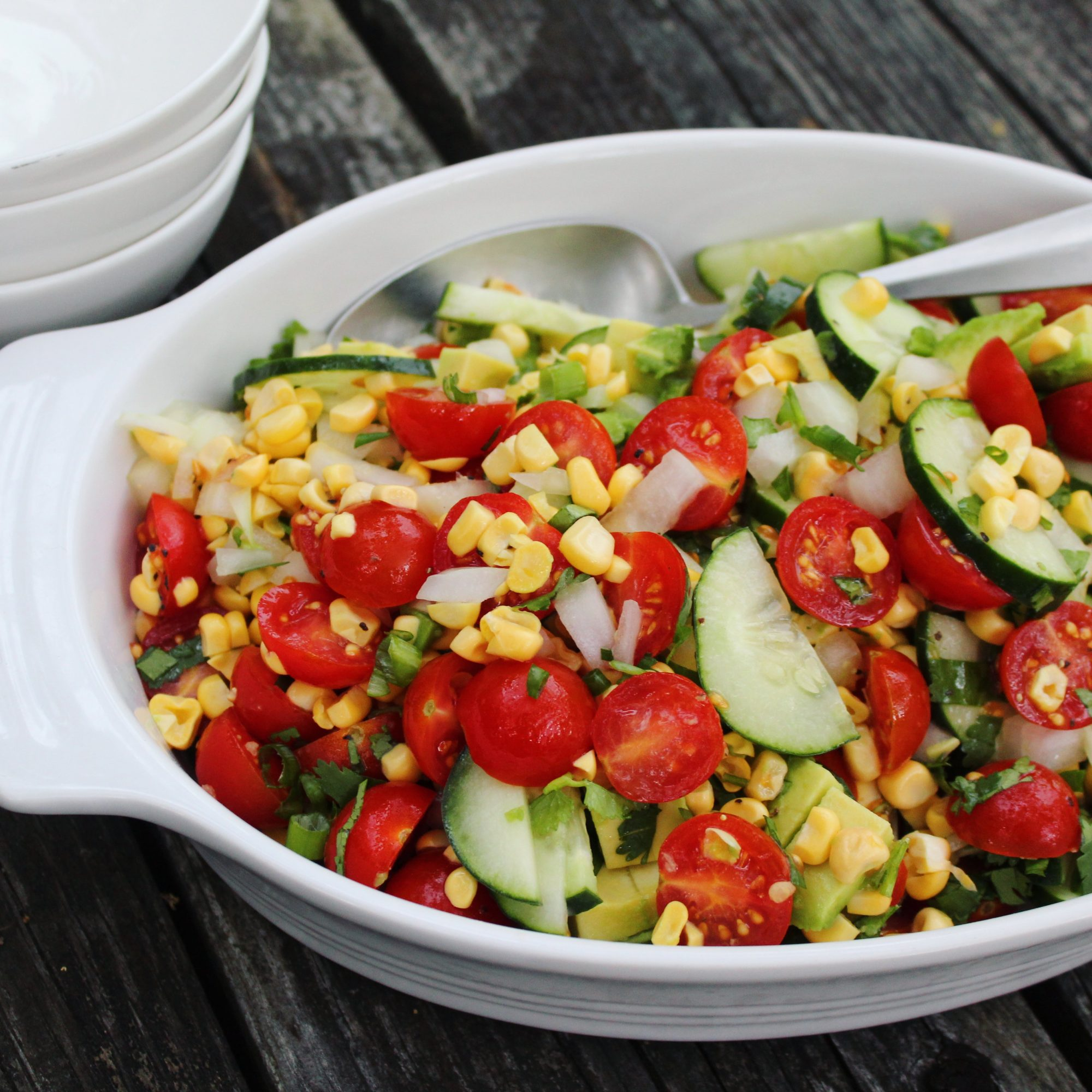 a two-handled white bowl with Raw Corn Salad and a spoon