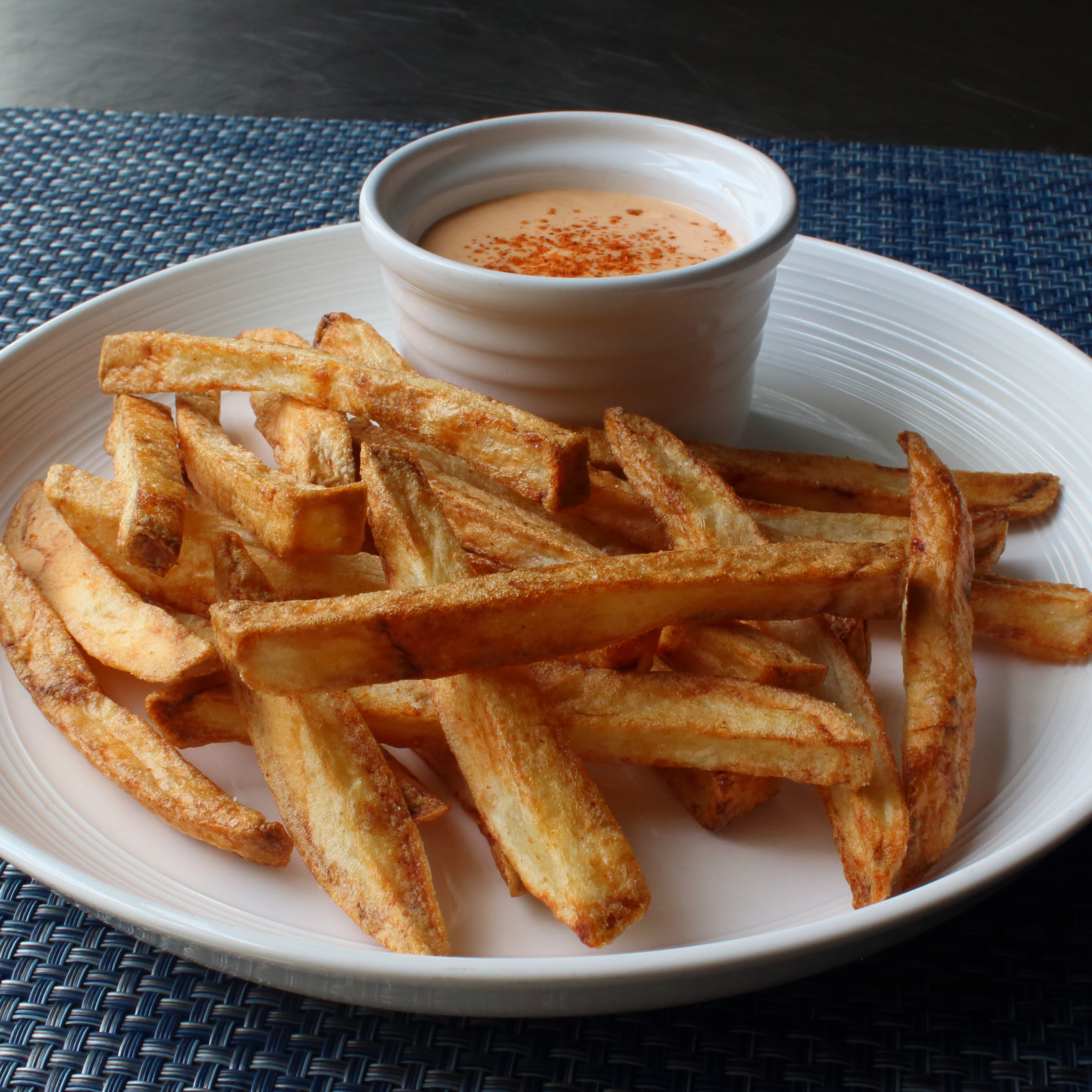 a plate of Air Fryer French Fries with a cup of dipping sauce