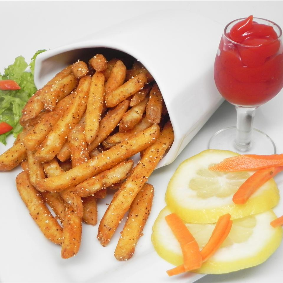 a paper cone of Cajun Baked French Fries with a cup of ketchup
