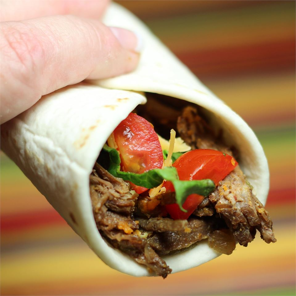 a rolled taco filled with Charley's Slow Cooker Mexican Style Meat, lettuce, and tomatoes
