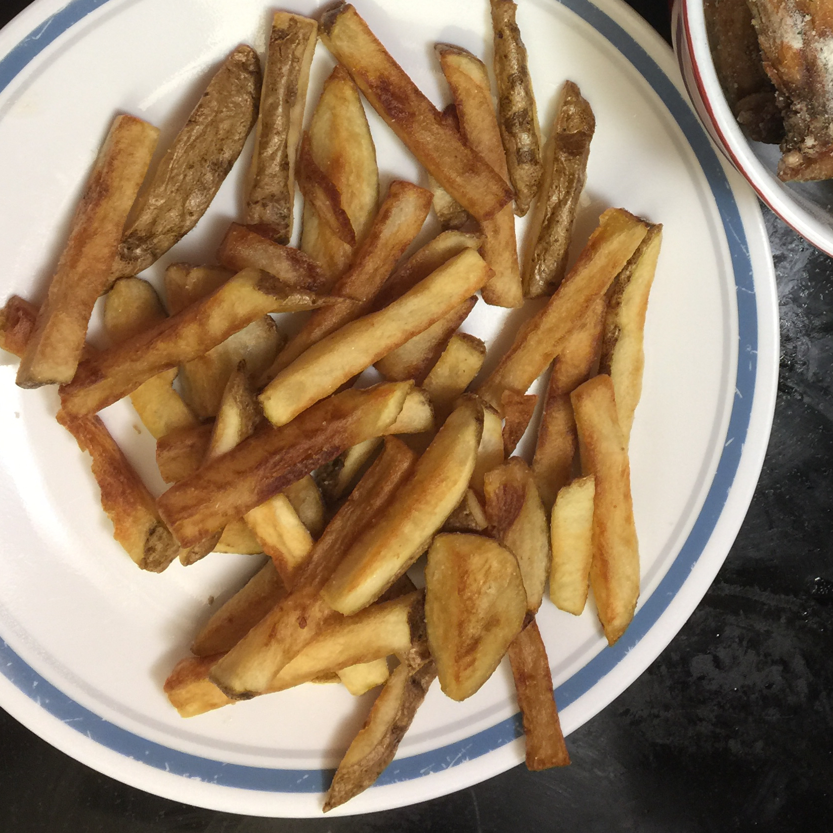 Chef John's French Fries on a white plate with a blue rim