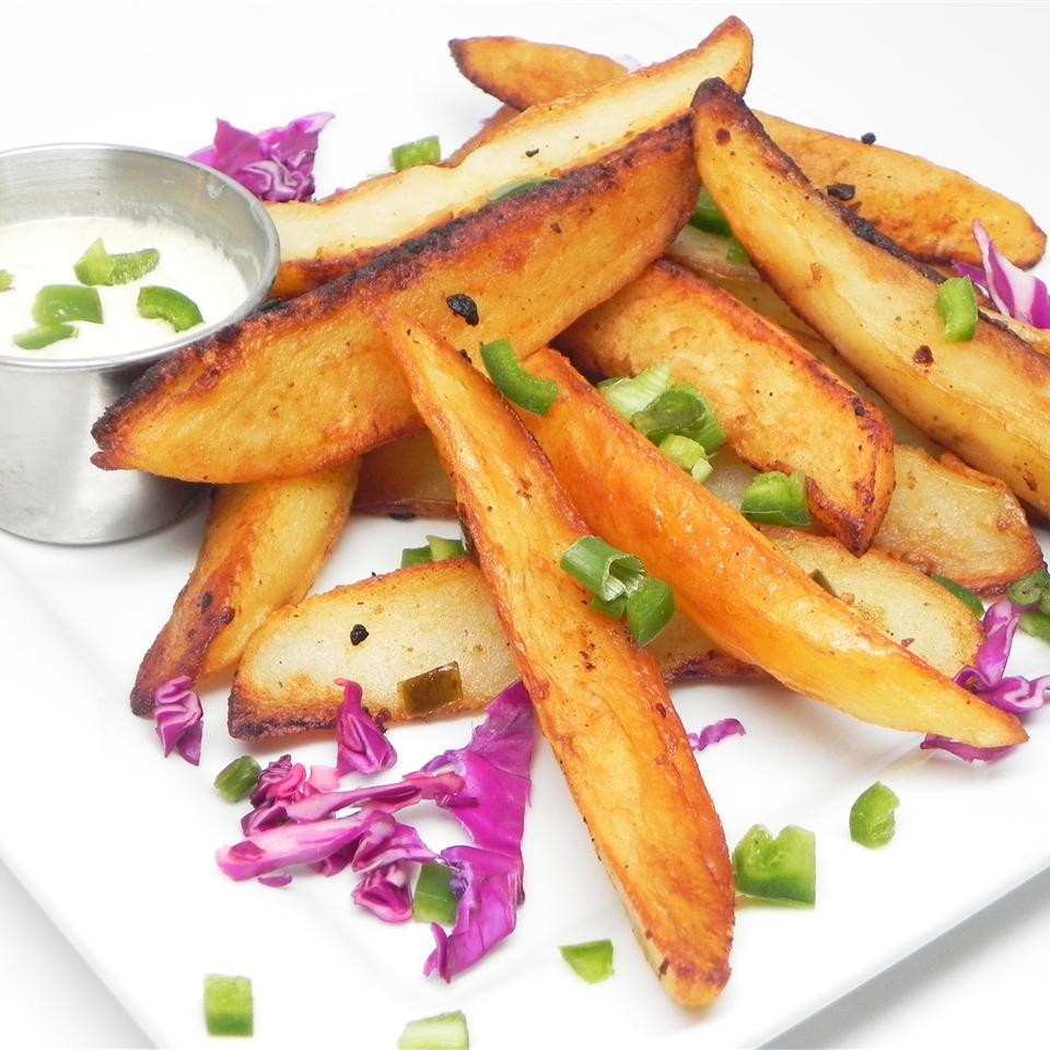 a plate of Nene's Jalapeno Hot Fries with chives sprinkled and a cup of dipping sauce