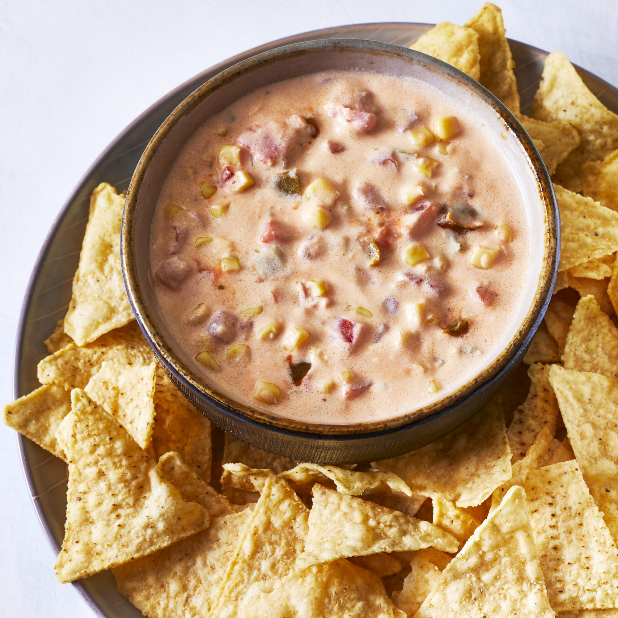a bowl of Warm Mexican Corn Dip surrounded by tortilla chips on a platter