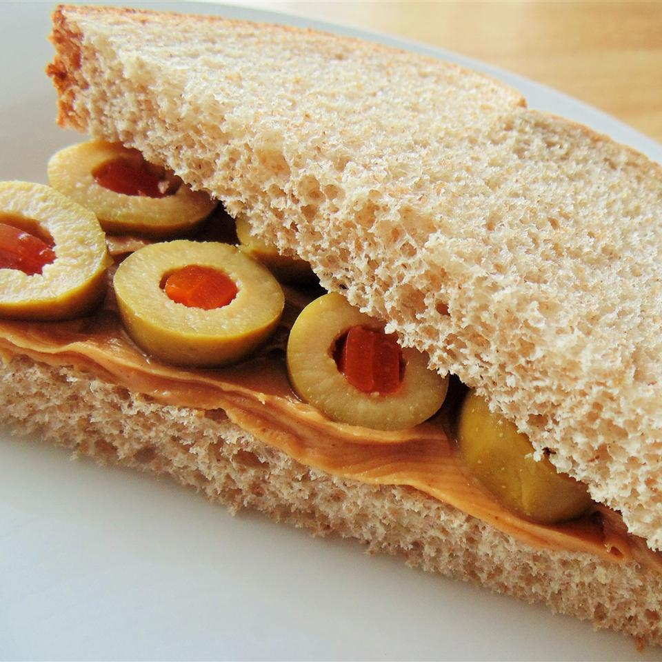 Close up of a peanut butter and olive sandwich