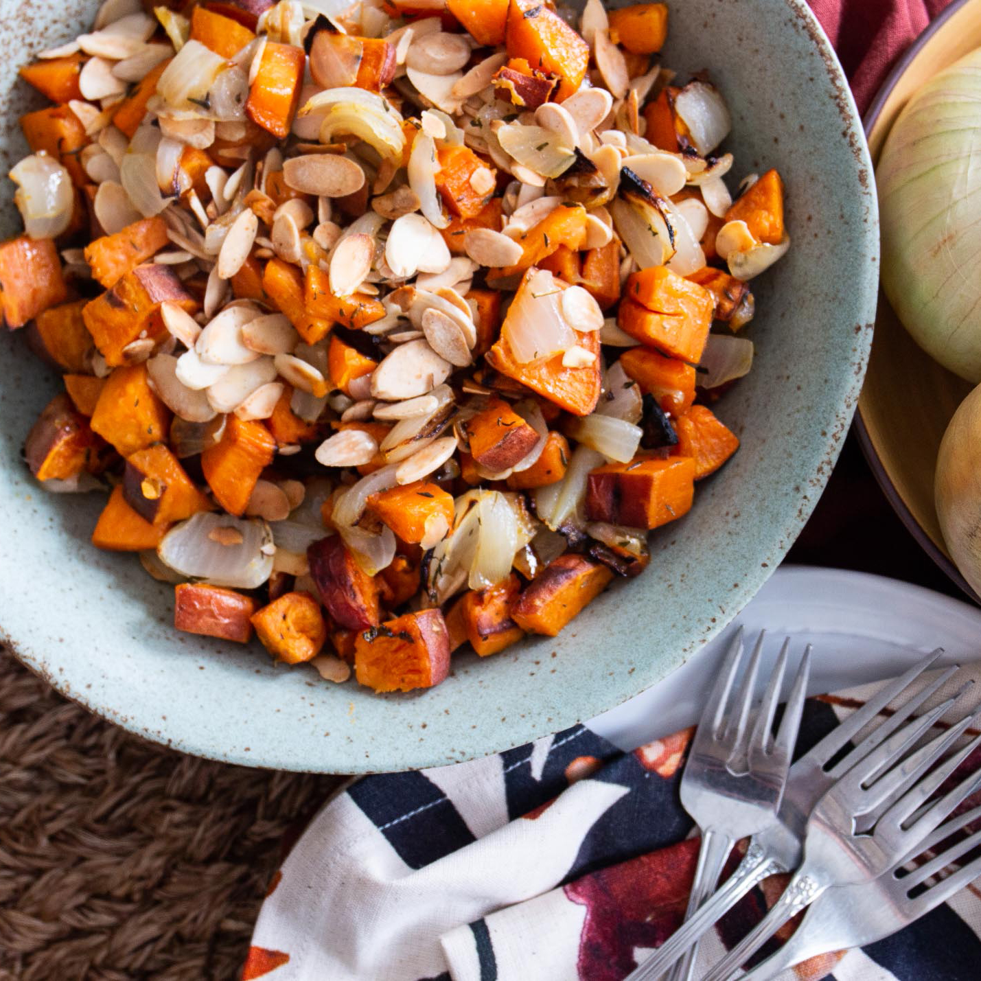 Roasted sweet potatoes and onions in a blue bowl
