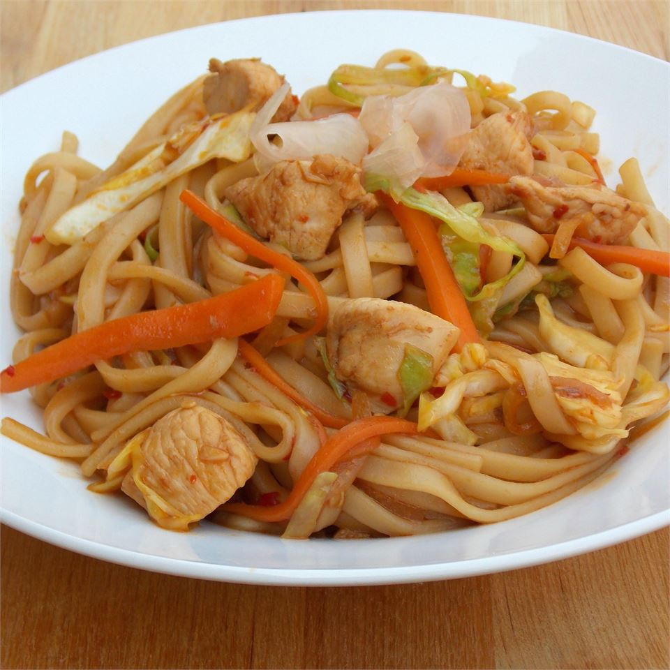 Chick stir fry with noodles and vegetables in white bowl