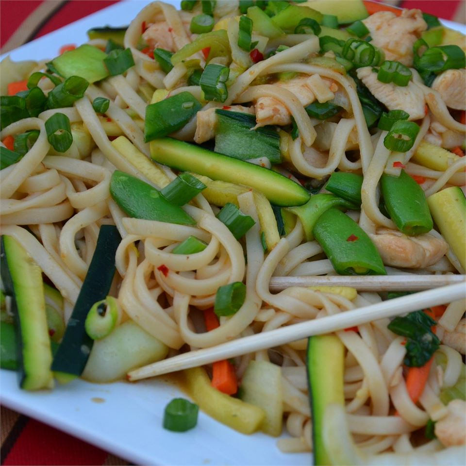 Chow mein, chicken, and vegetables with wooden chopsticks