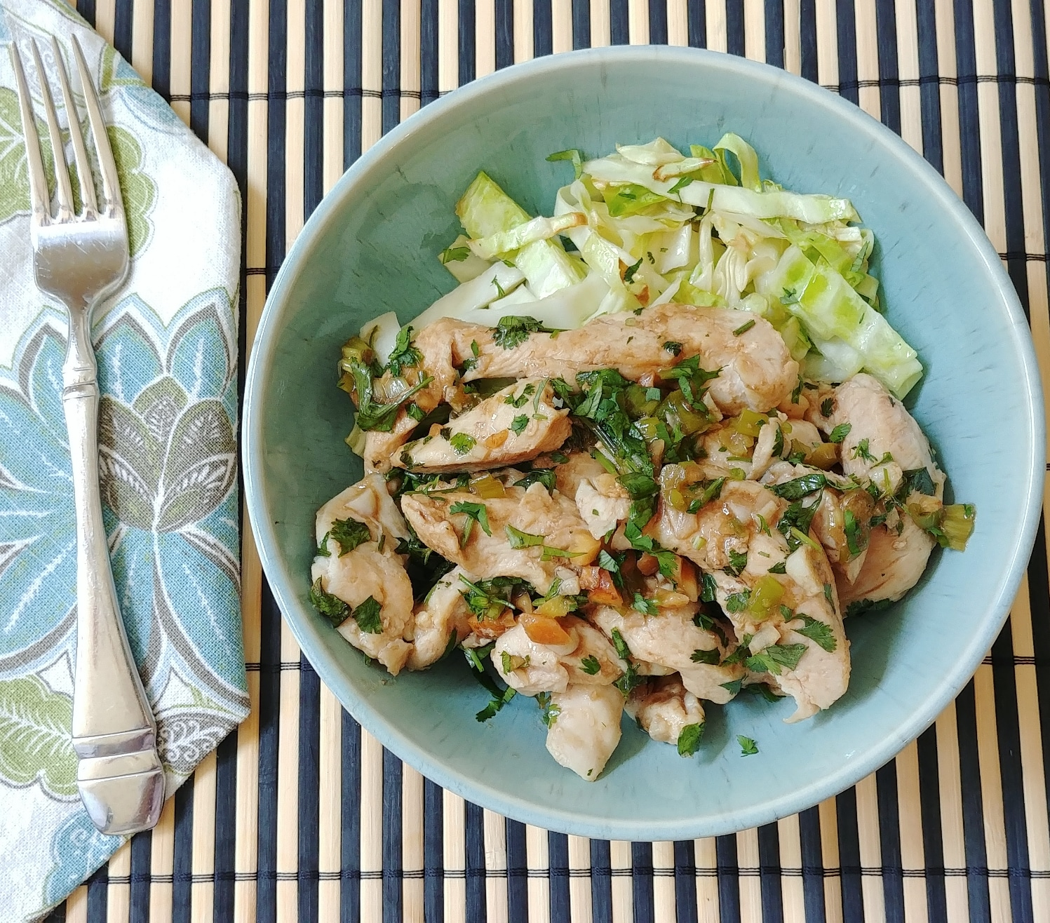 Cilantro Chicken with Peanuts in blue bowl next to napkin and fork