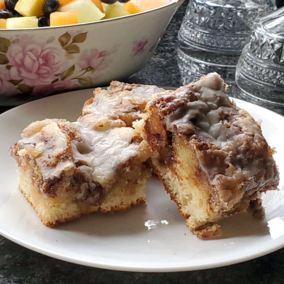 Two slices of Cinnabon® Cinnamon Roll Cake on a white plate