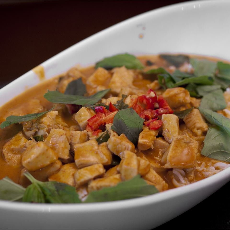 Curry chicken with basils in white bowl