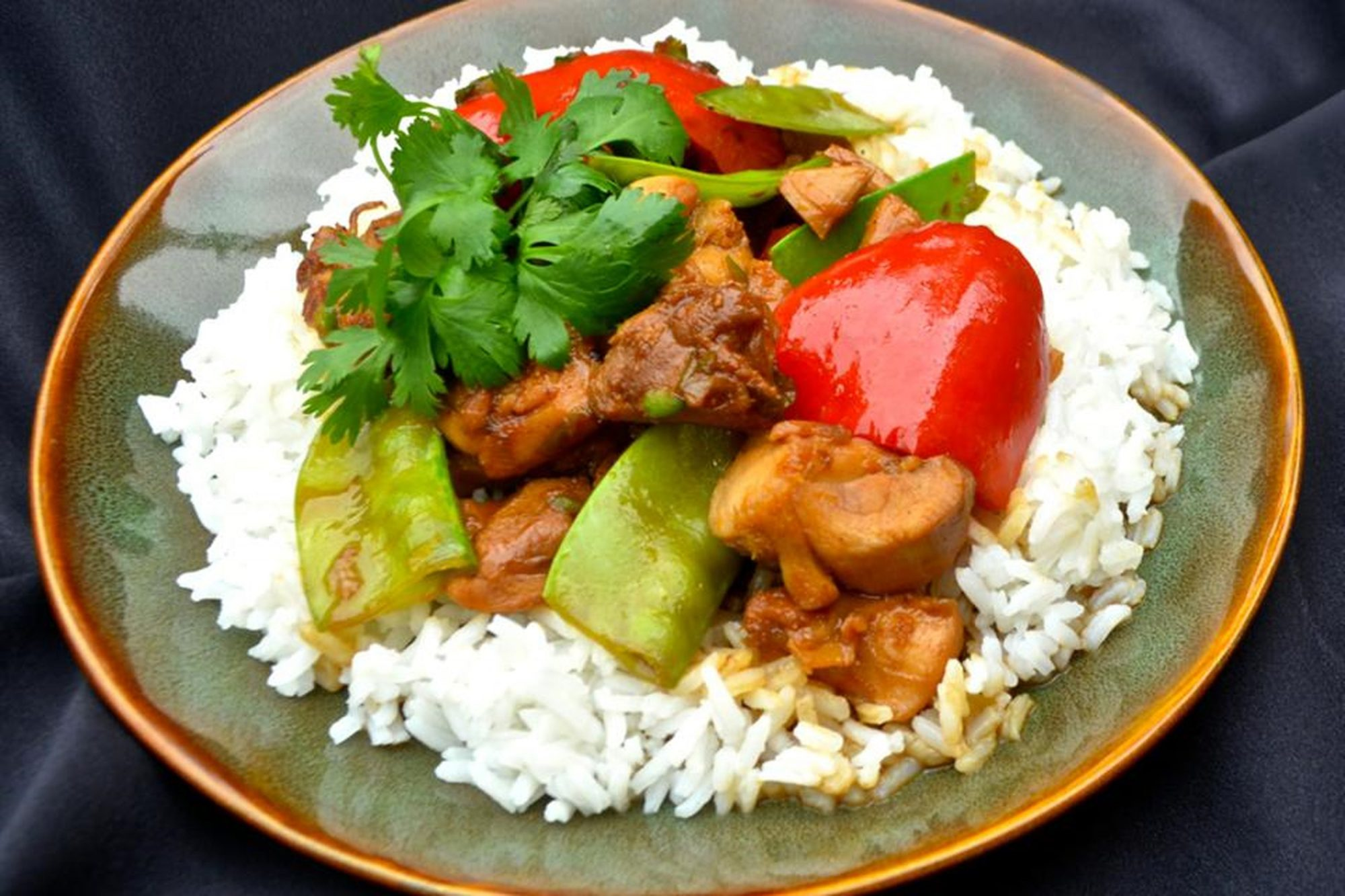 Orange chicken with vegetables over white rice on plate