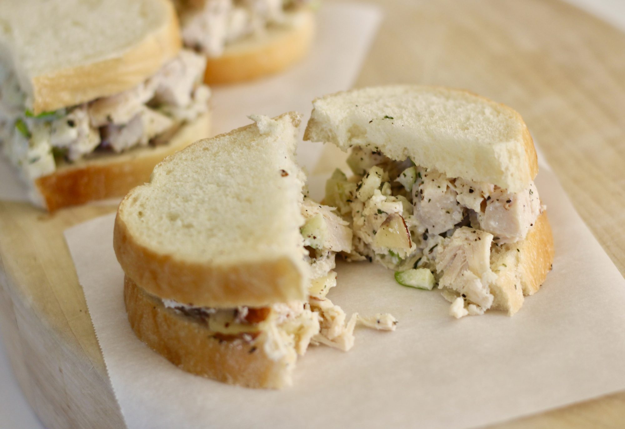 a picture of a Chicken Salad Tea Sandwich split in half on white parchment paper