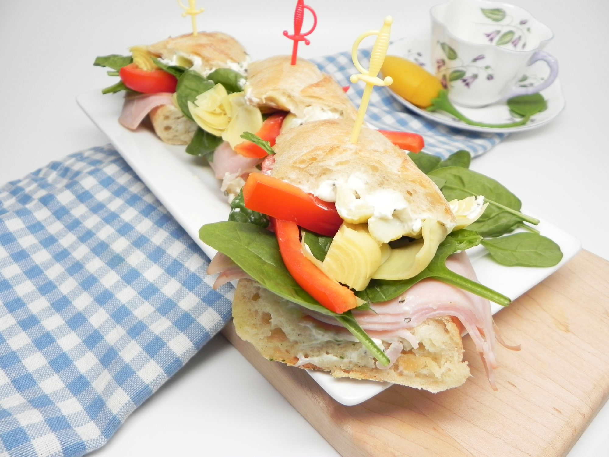 Make-Ahead Turkey Tea Sandwiches on a white platter with a blue gingham napkin