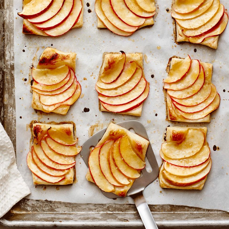 Apple Tartlets over parchment paper on a sheet pan