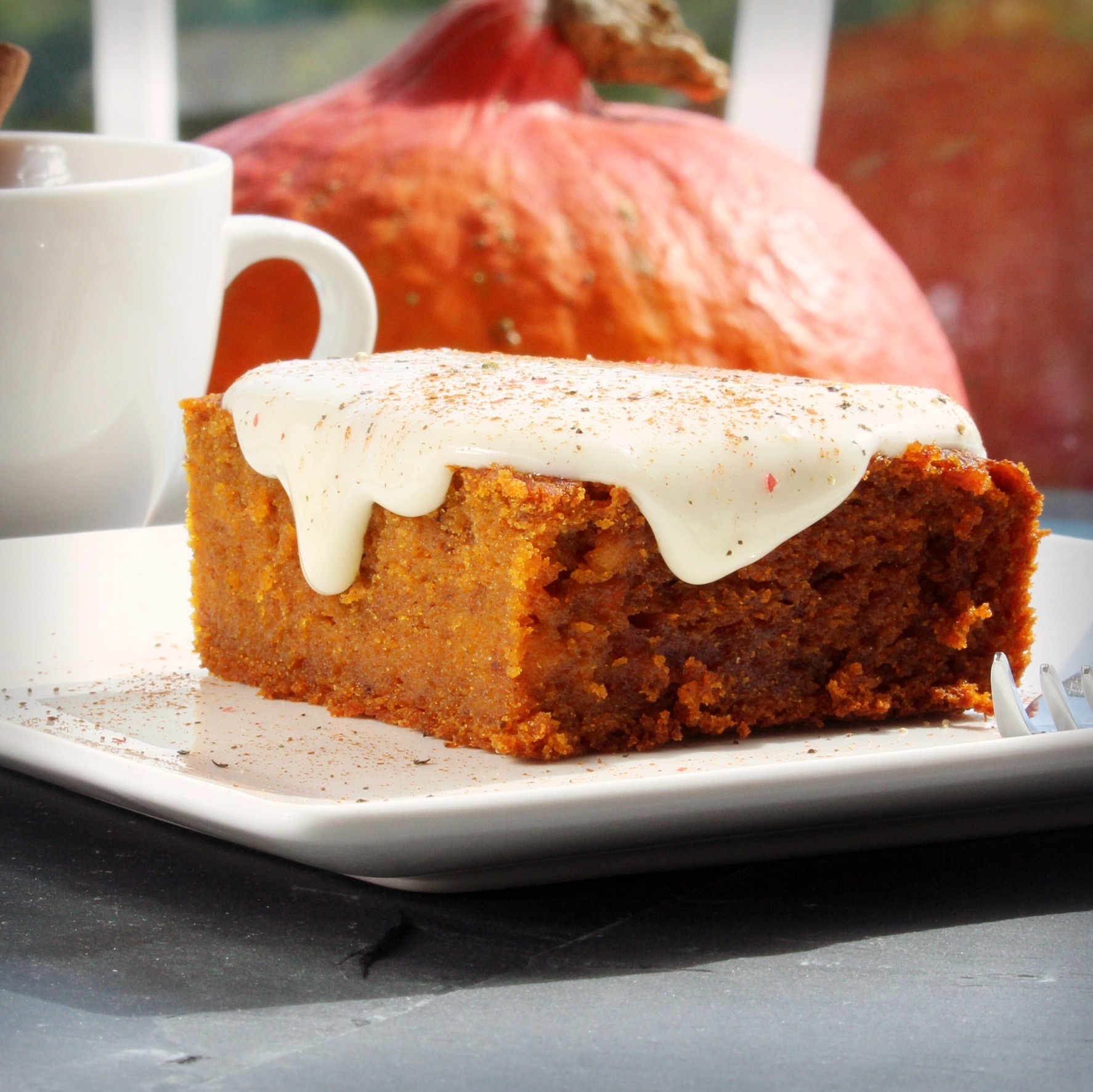 Pumpkin Squares on a white plate with a pumpkin and white mug in the background