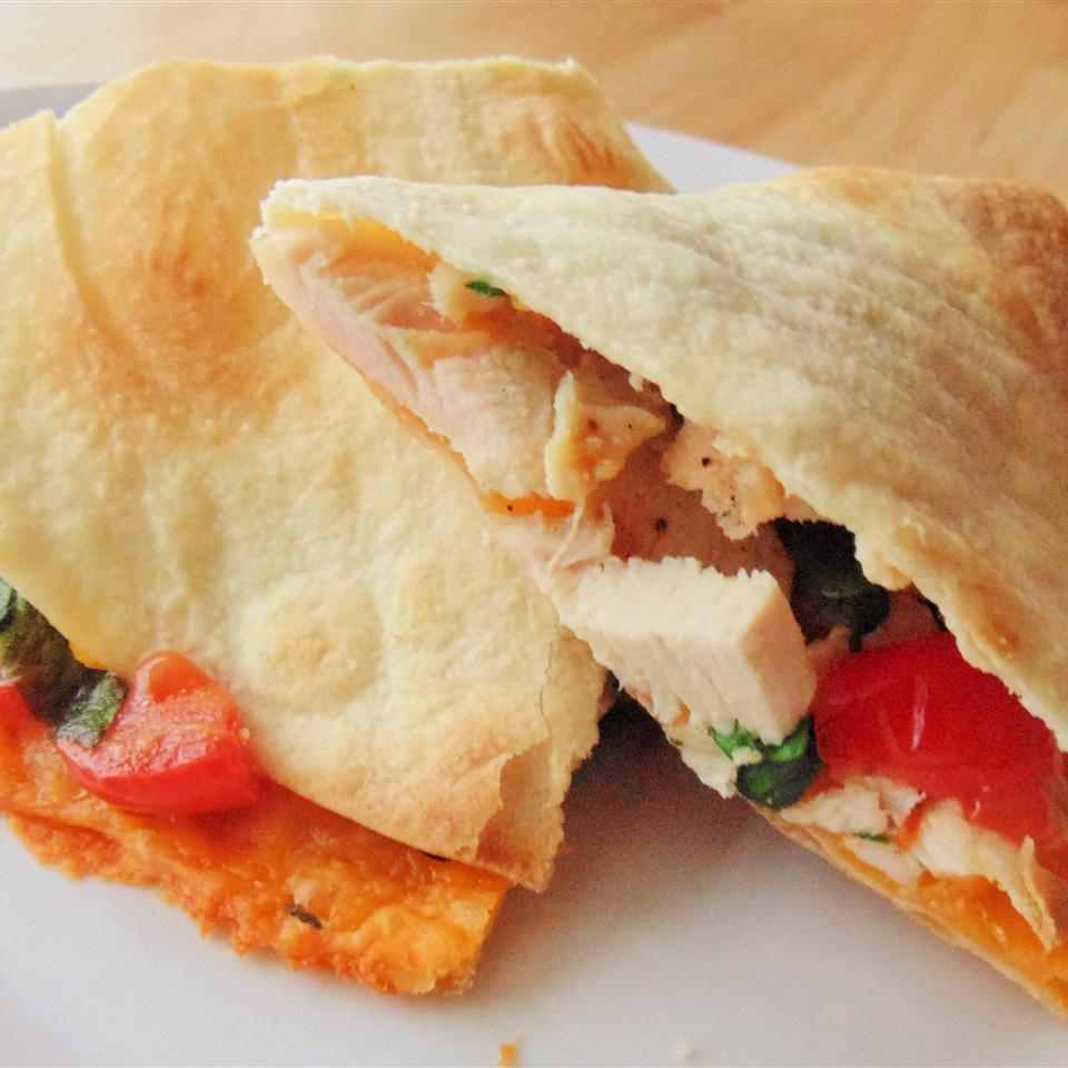 Chicken, tomato, and spinach quesadilla on white plate