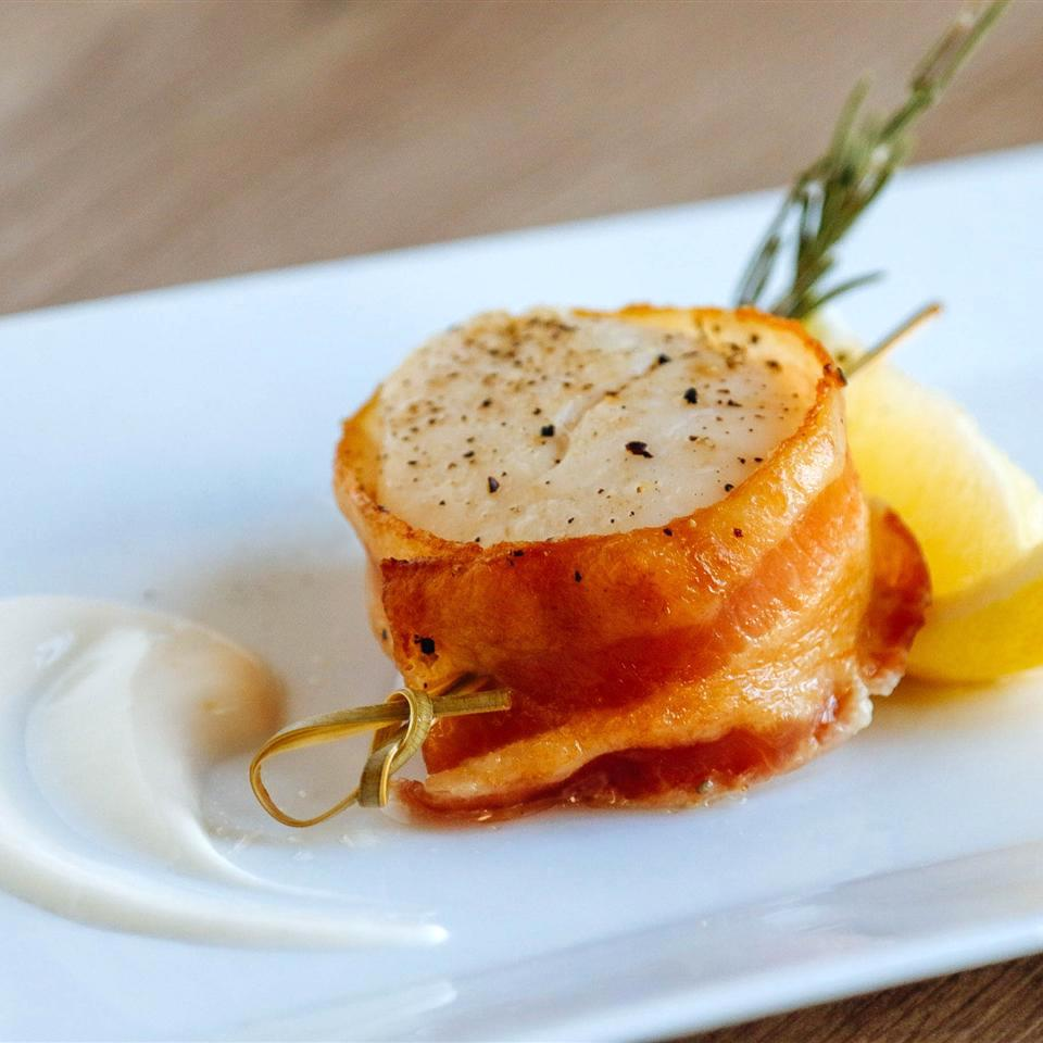 one scallop wrapped in bacon with lemon and rosemary garnish