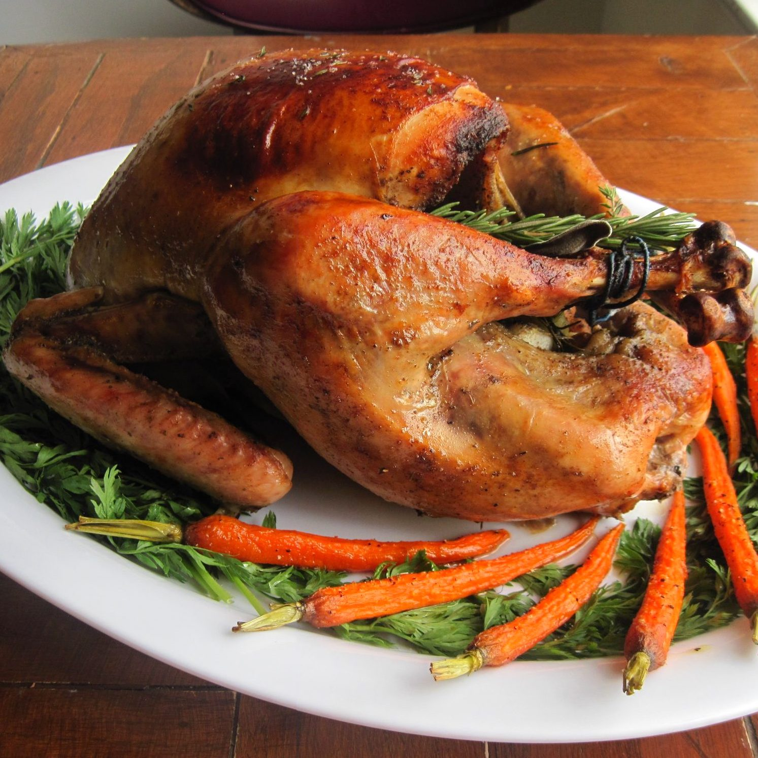 whole roasted turkey on a white serving dish with carrots