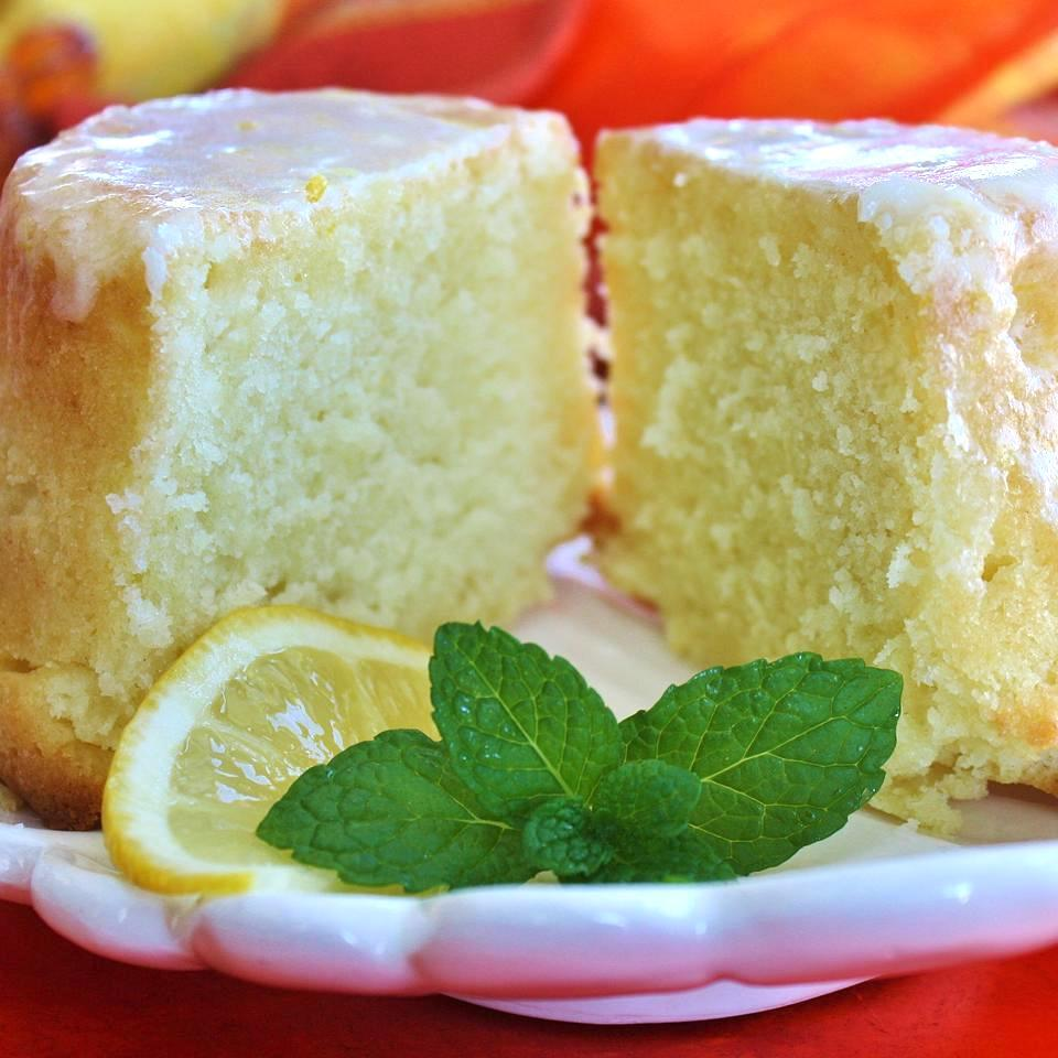 pound cake on a white plate with glaze, lemon slice, and mint garnish