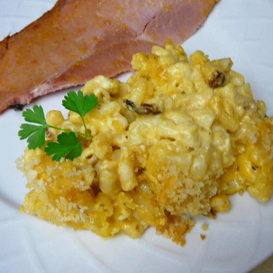 A serving of macaroni and cheese on a plate with a slice of ham