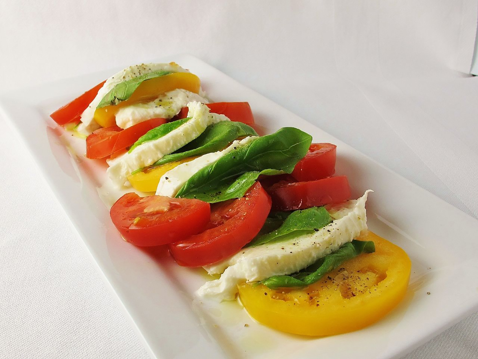 Slices of ripe red and yellow tomatoes alternating with fresh mozzarella and basil