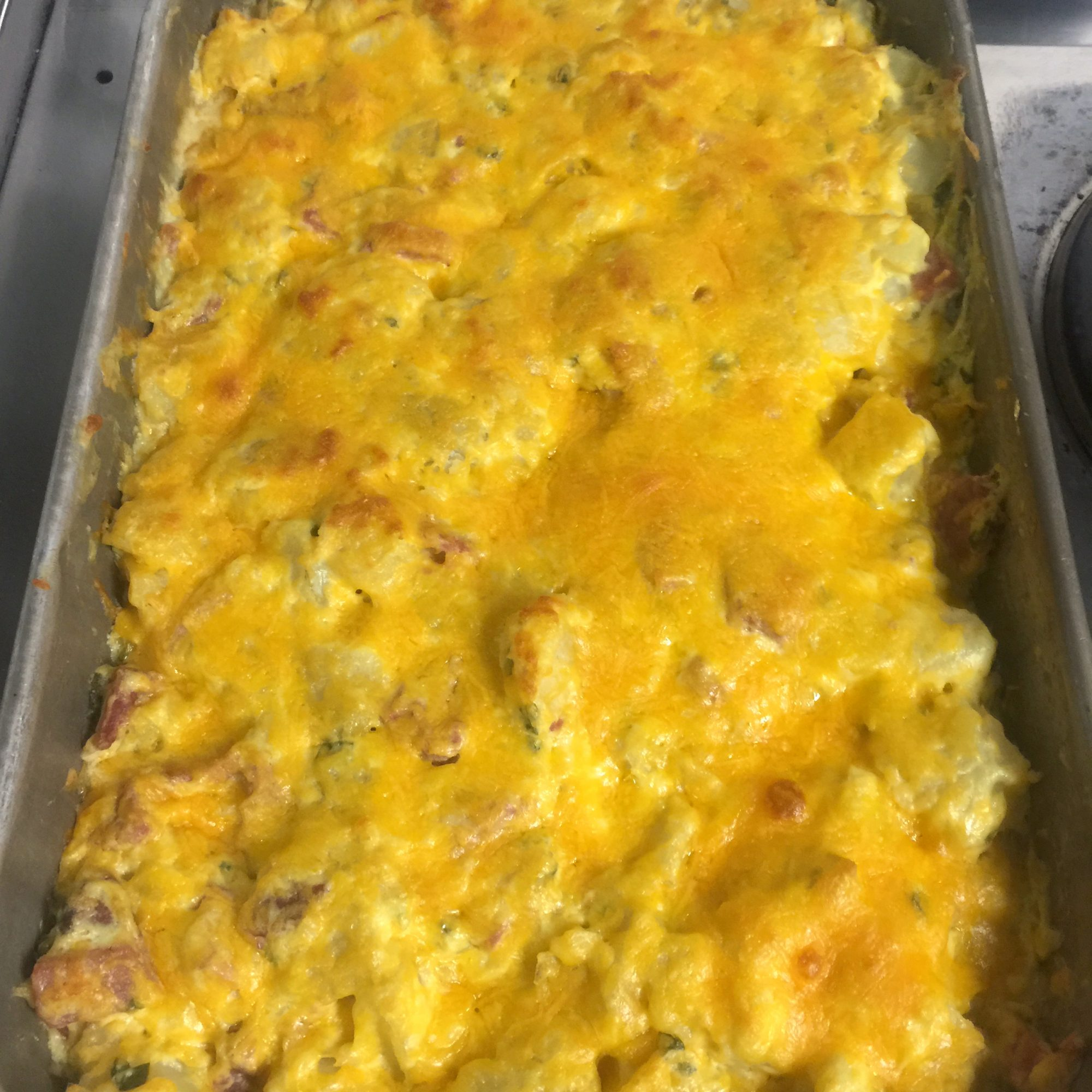 pan of cheese-covered Easy Sour Cream Scalloped Potatoes