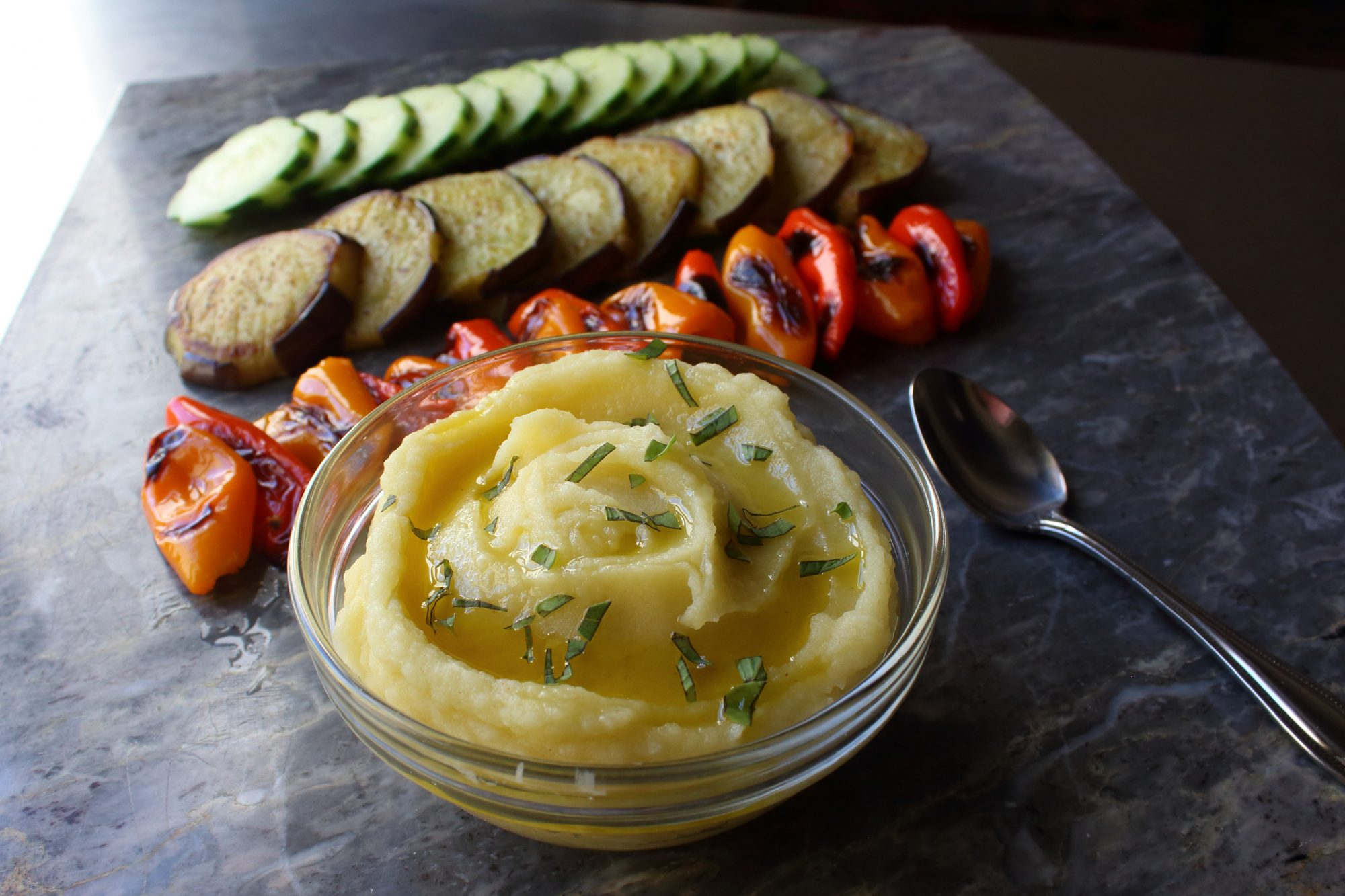 A small glass bowl of dip served with roasted red peppers, eggplant slices, and fresh cucumbers