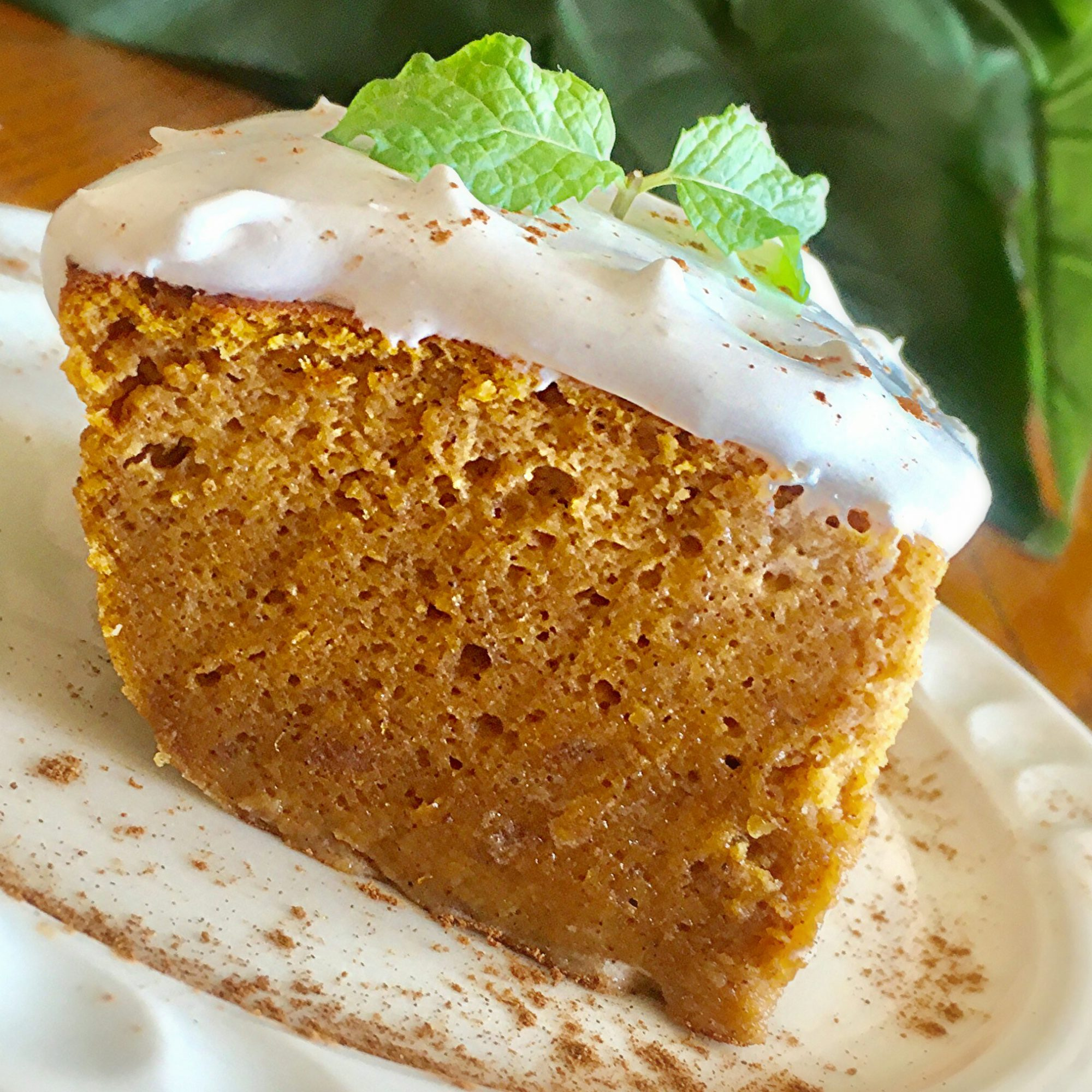 Pumpkin Magic Cake with Maple Cinnamon Whipped Cream on a white plate with mint garnish