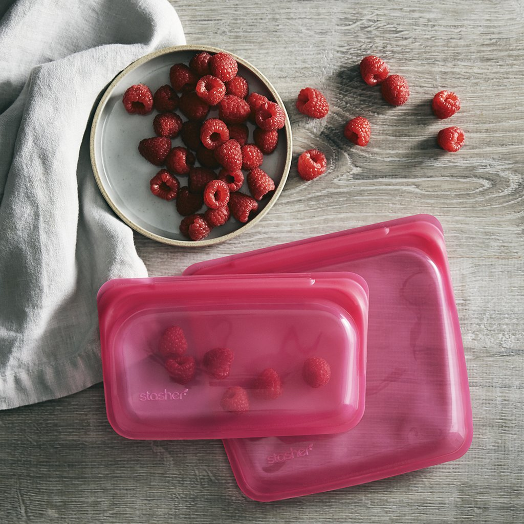 Stasher pink bag with raspberries inside and a bowl of raspberries