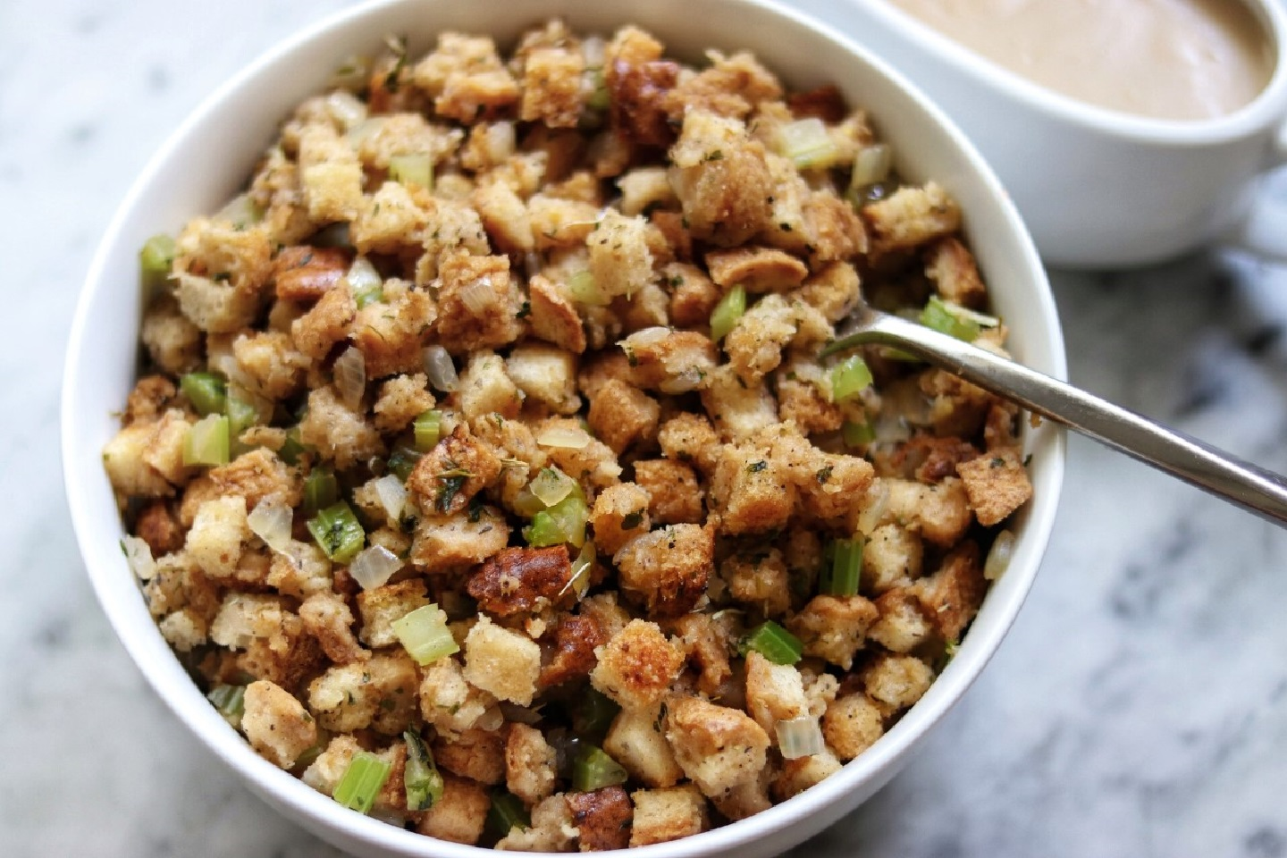 Better-than-Boxed Vegan and Gluten-Free Stuffing in white bowl on white granite countertop