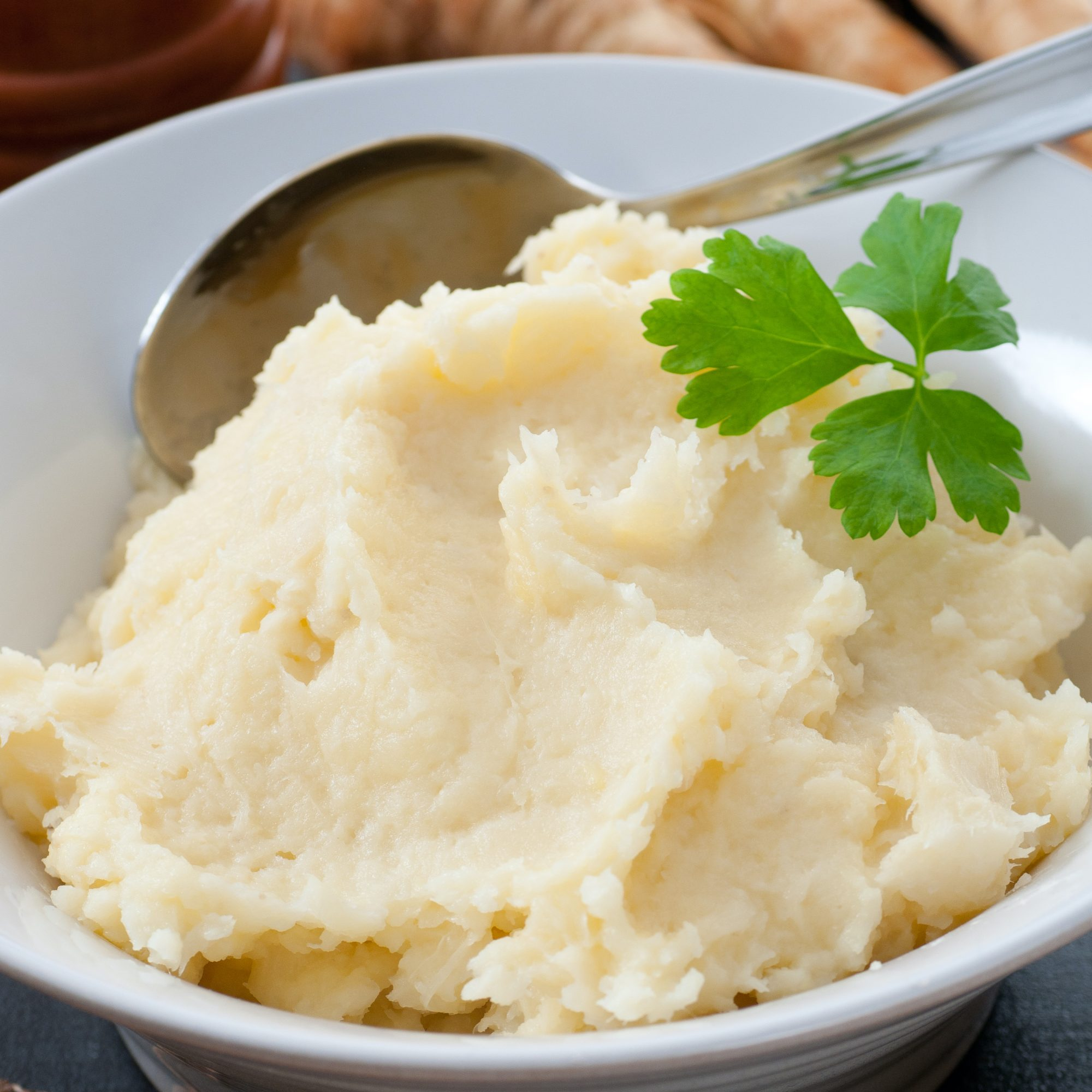 mashed turnips in a white bowl with parsley garnic