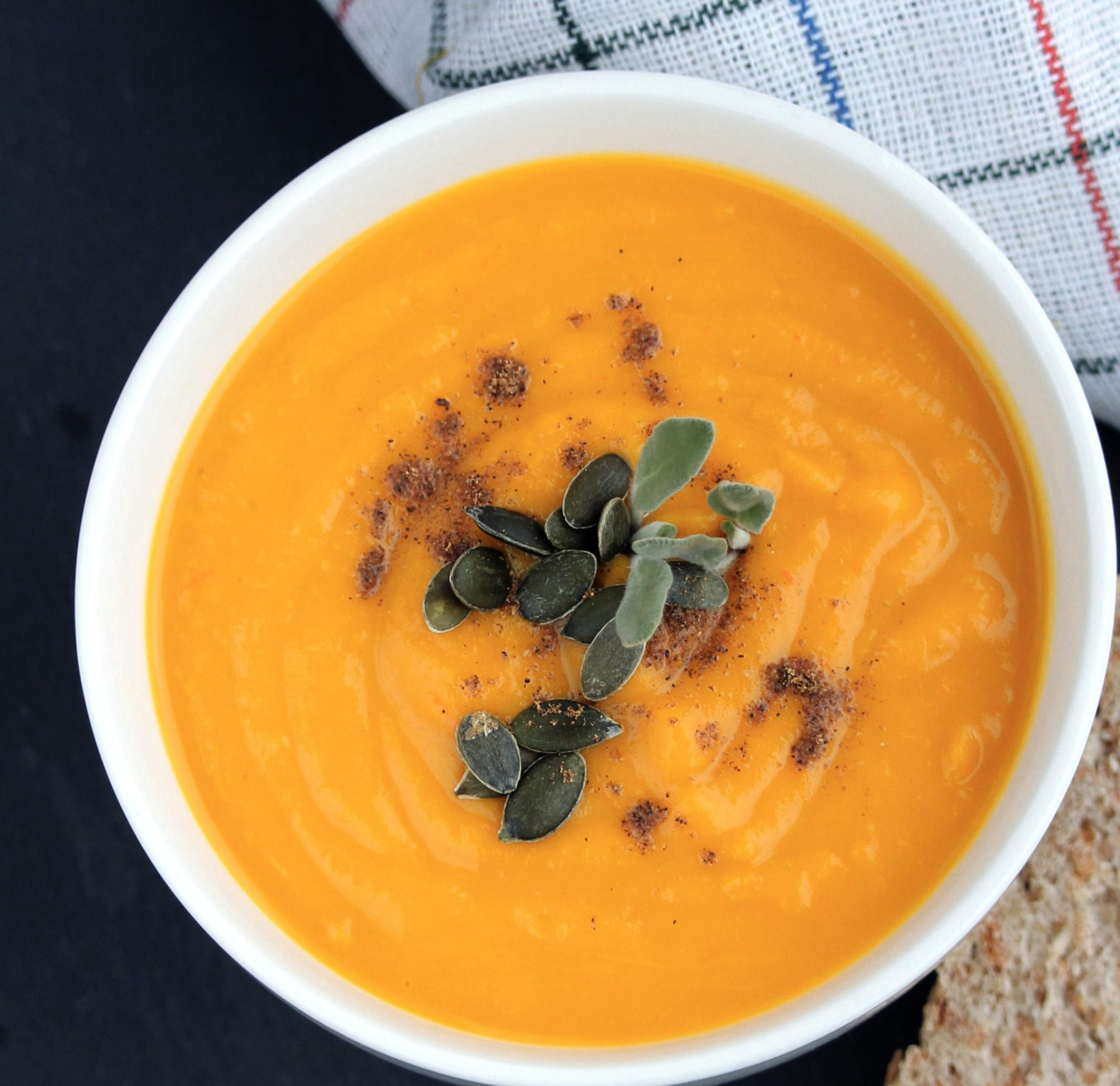 Roasted pumpkin soup in white bowl with pumpkin seeds on top