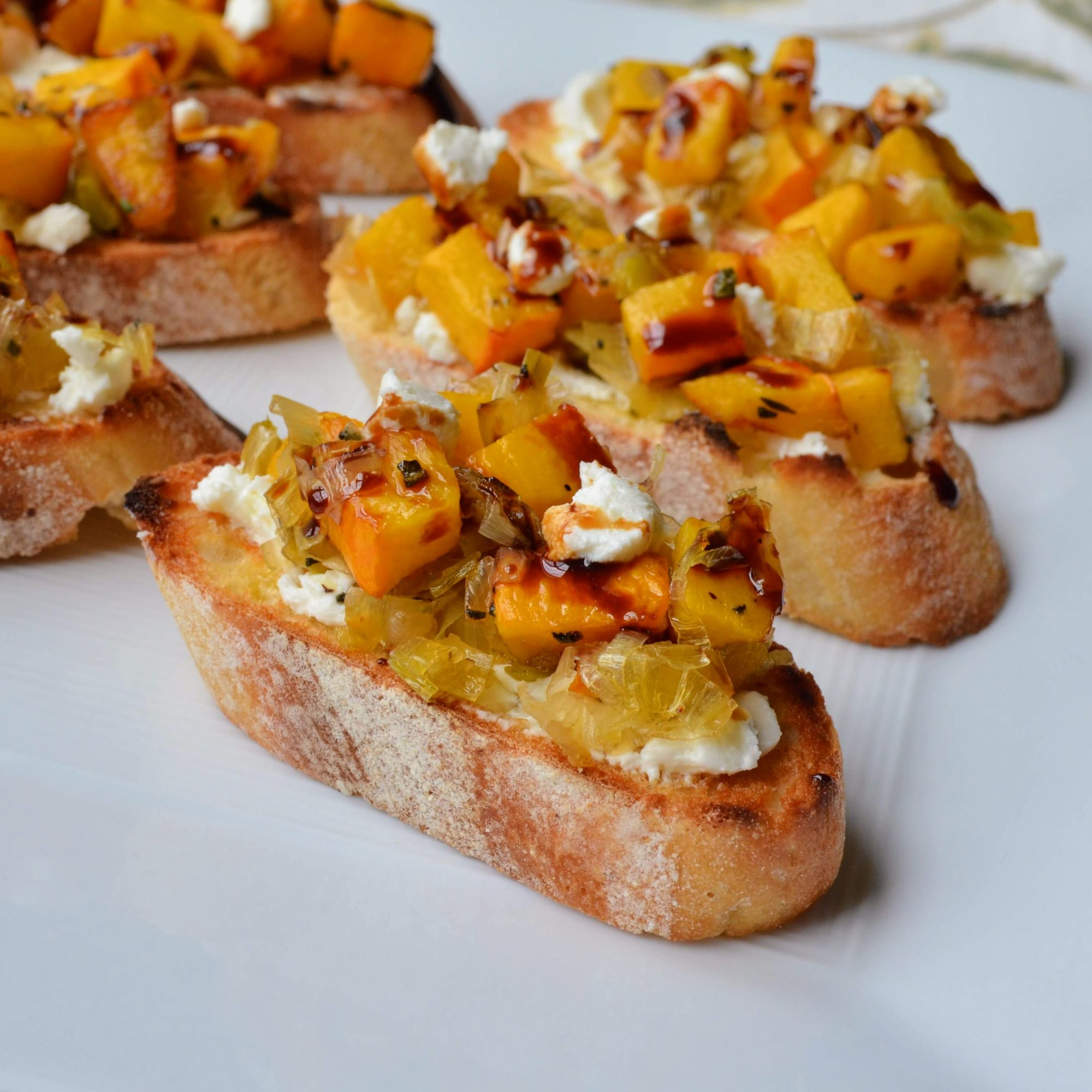 Roasted Pumpkin and Goat Cheese Crostinis on white plate