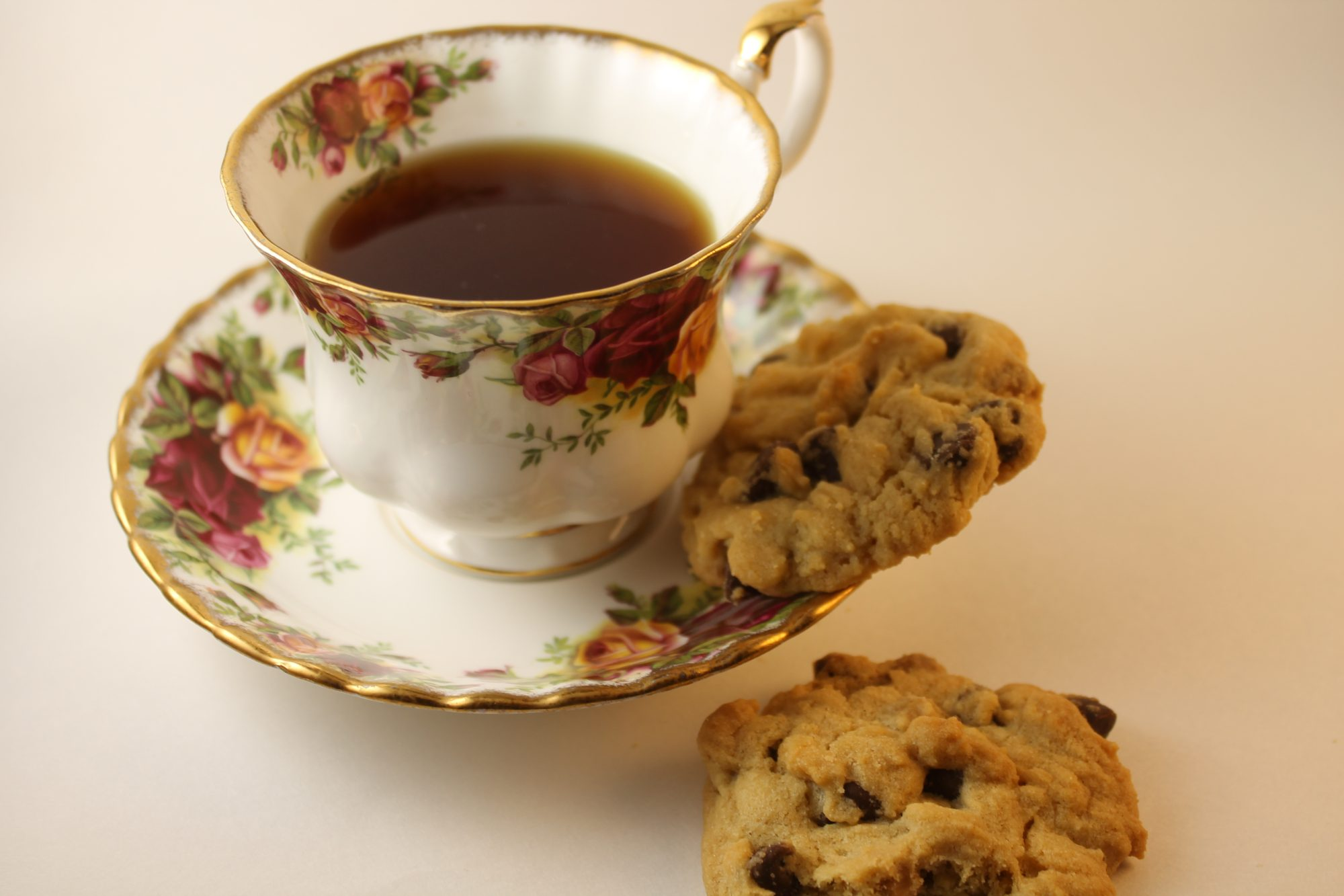 Ginger tea in floral tea cup on tea plate with two cookies